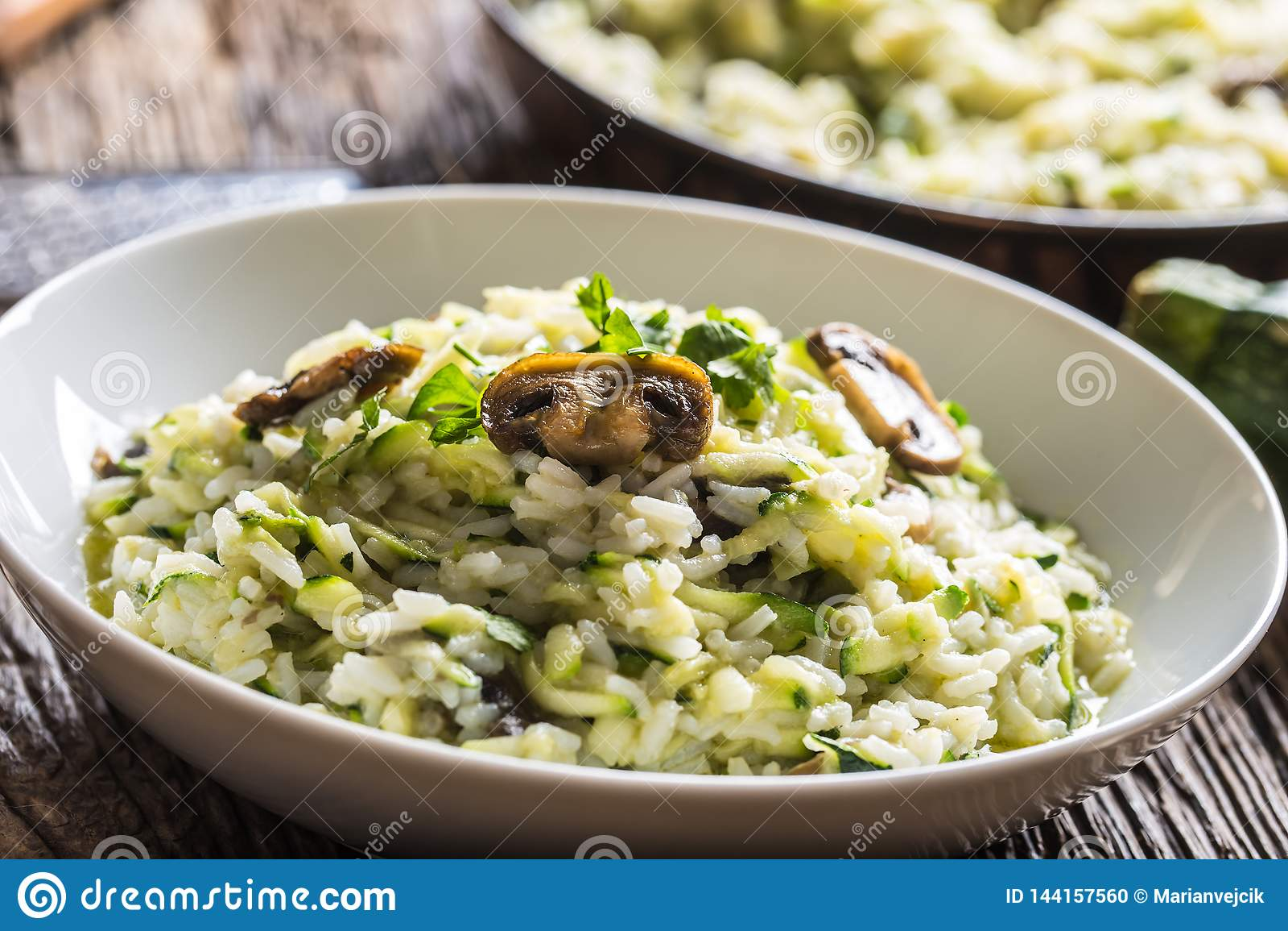 意大利意大利煨饭夏南瓜蘑菇和巴马干酪在白色板材