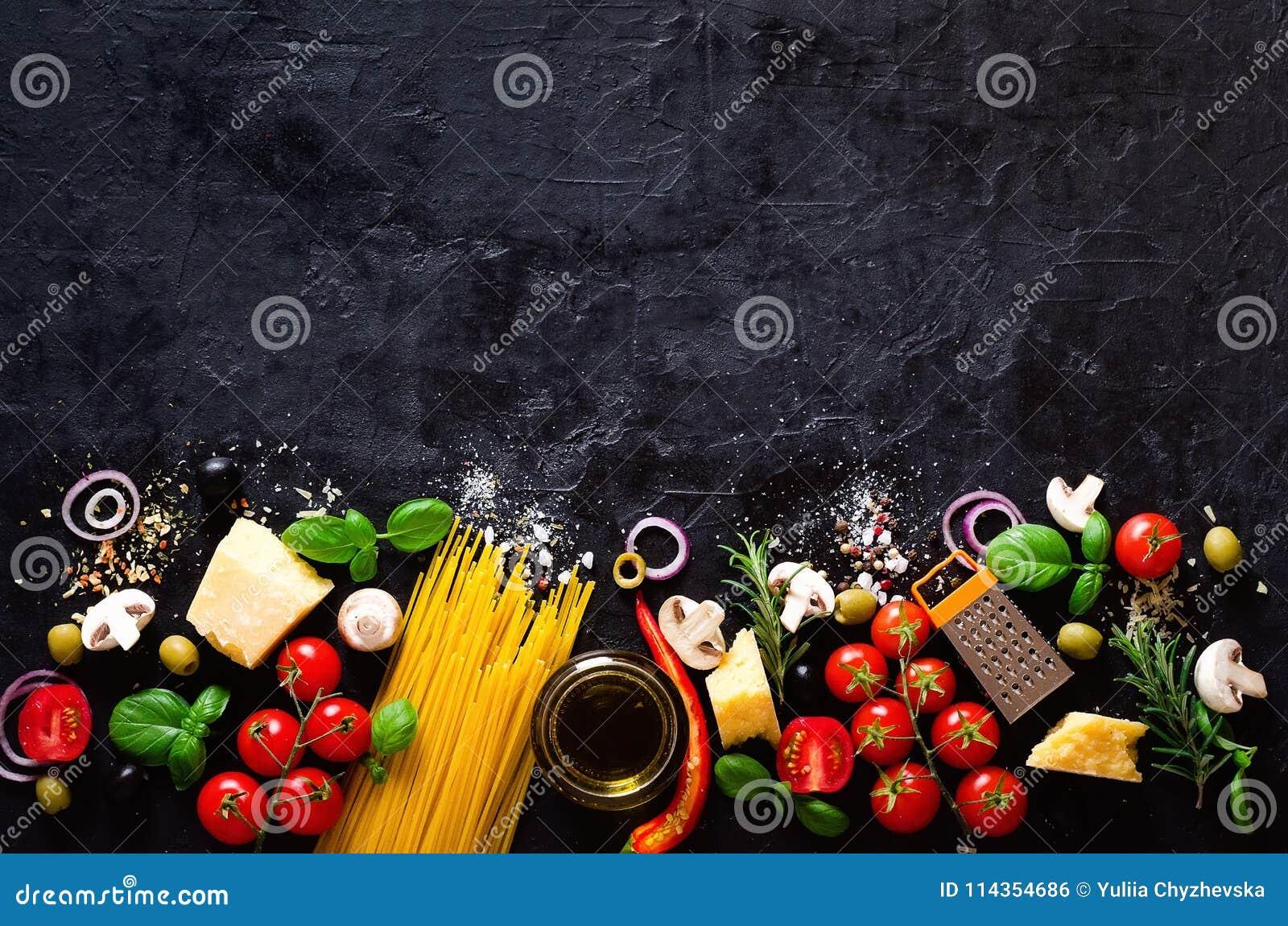意大利面团的,在黑石板岩背景的意粉食品成分 复制您的文本空间