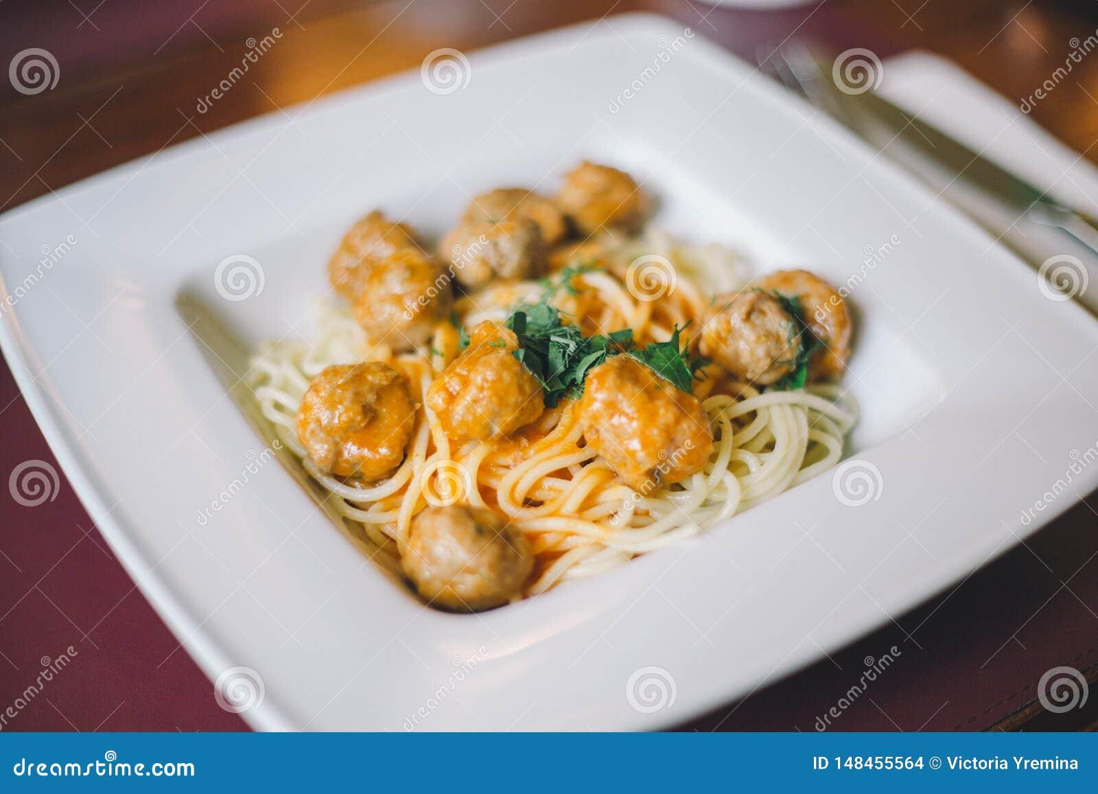 意粉面团特写镜头用丸子和西红柿酱在一块白色板材在桌上