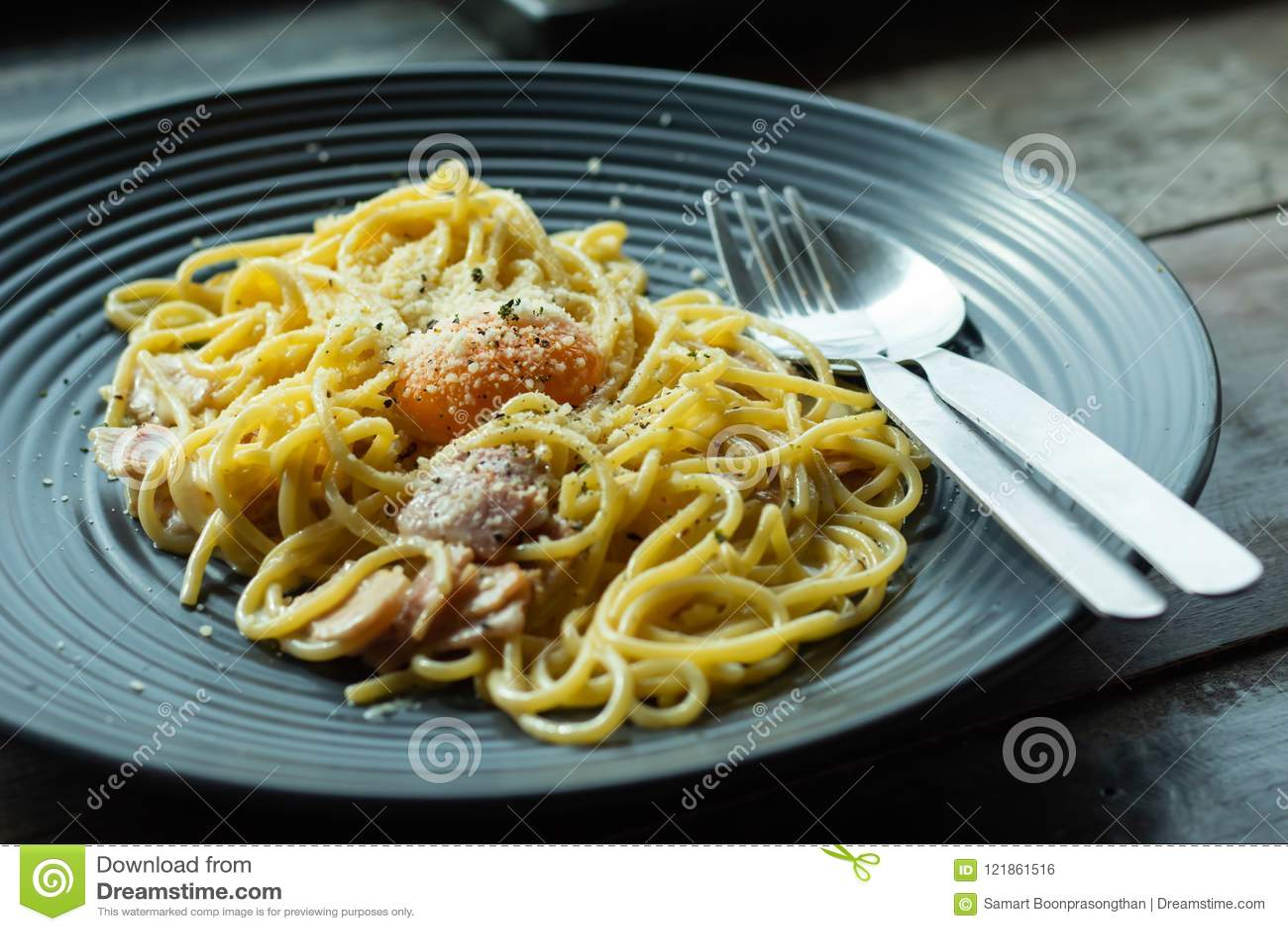 意粉,在一个黑色的盘子的油煎的乳酪在桌上