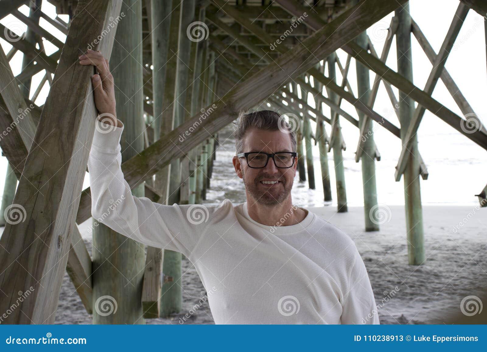 愚蠢海滩南卡罗来纳, 2018年2月17日-站立在海滩码头下的长袖的白色衬衣的人