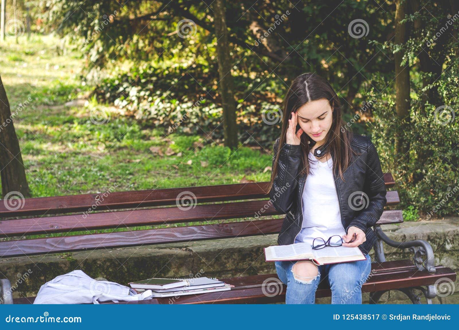 感到年轻学院或学校的女孩恶心与强的头疼痛苦或偏头痛攻击,当她坐长凳在公园时