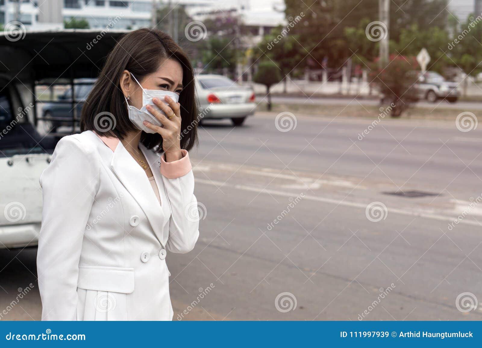 感到的防毒面具的亚裔妇女坏在街道上在有大气污染的城市 黑短发遭受病残和我们