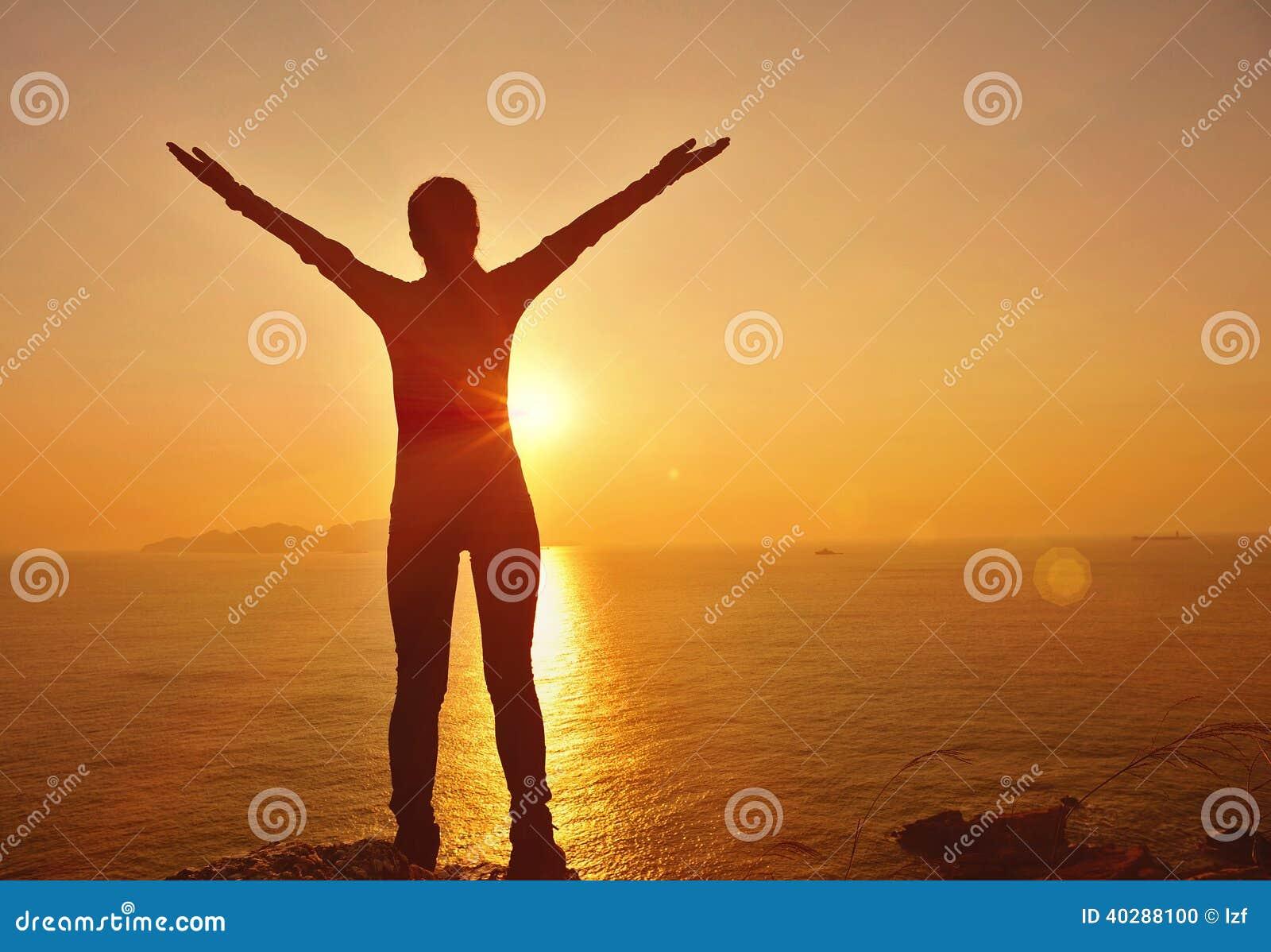 感激的对日出的妇女开放胳膊