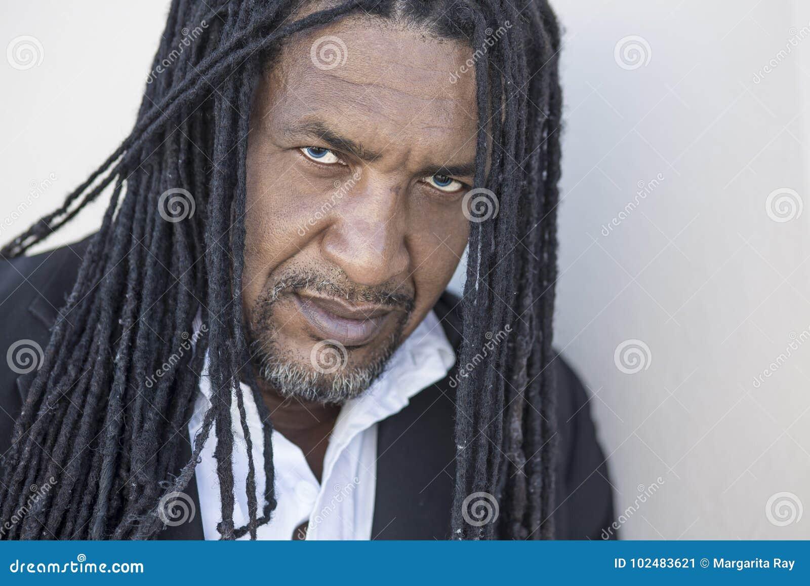 成人坚强的黑人画象有长的dreadlocks和蓝眼睛的