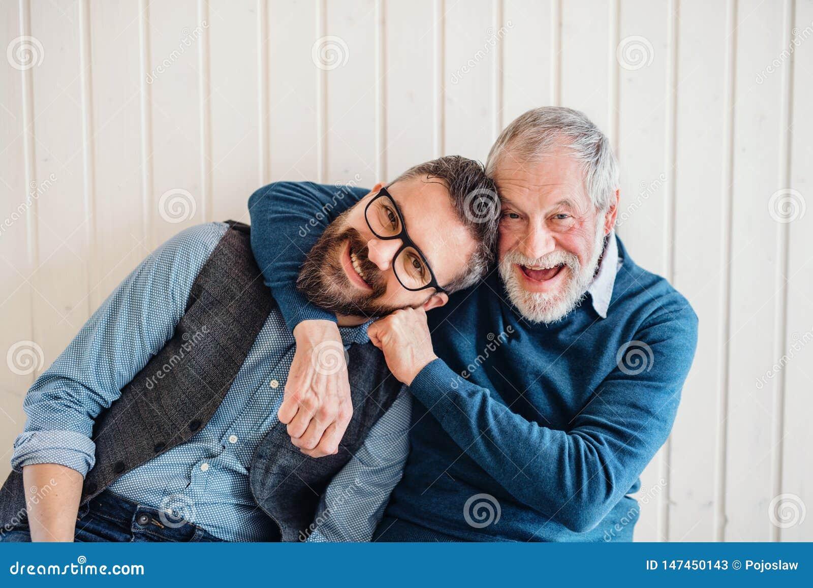 成人行家儿子和资深父亲画象坐地板户内在家