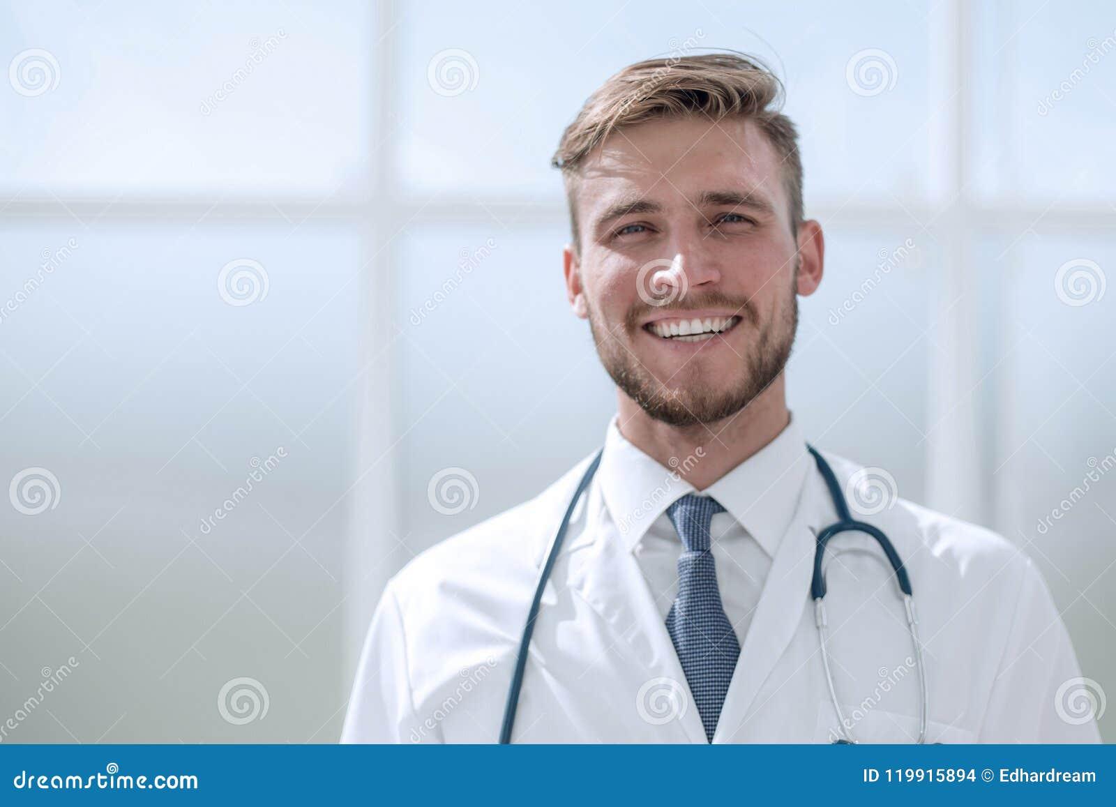 成功的医生治疗师,站立在窗口附近