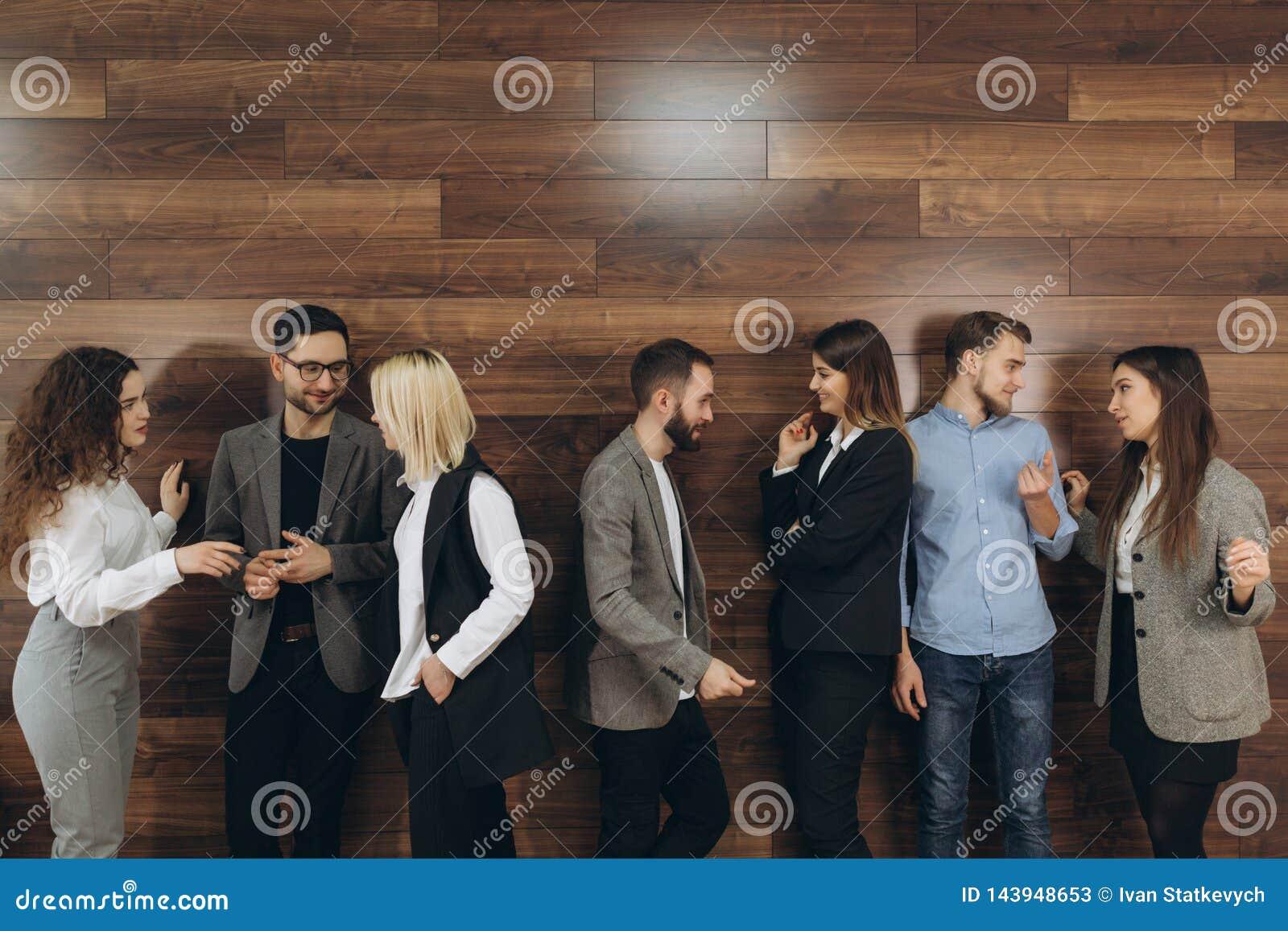 成功的年轻商人是谈话和微笑在咖啡休息期间在办公室