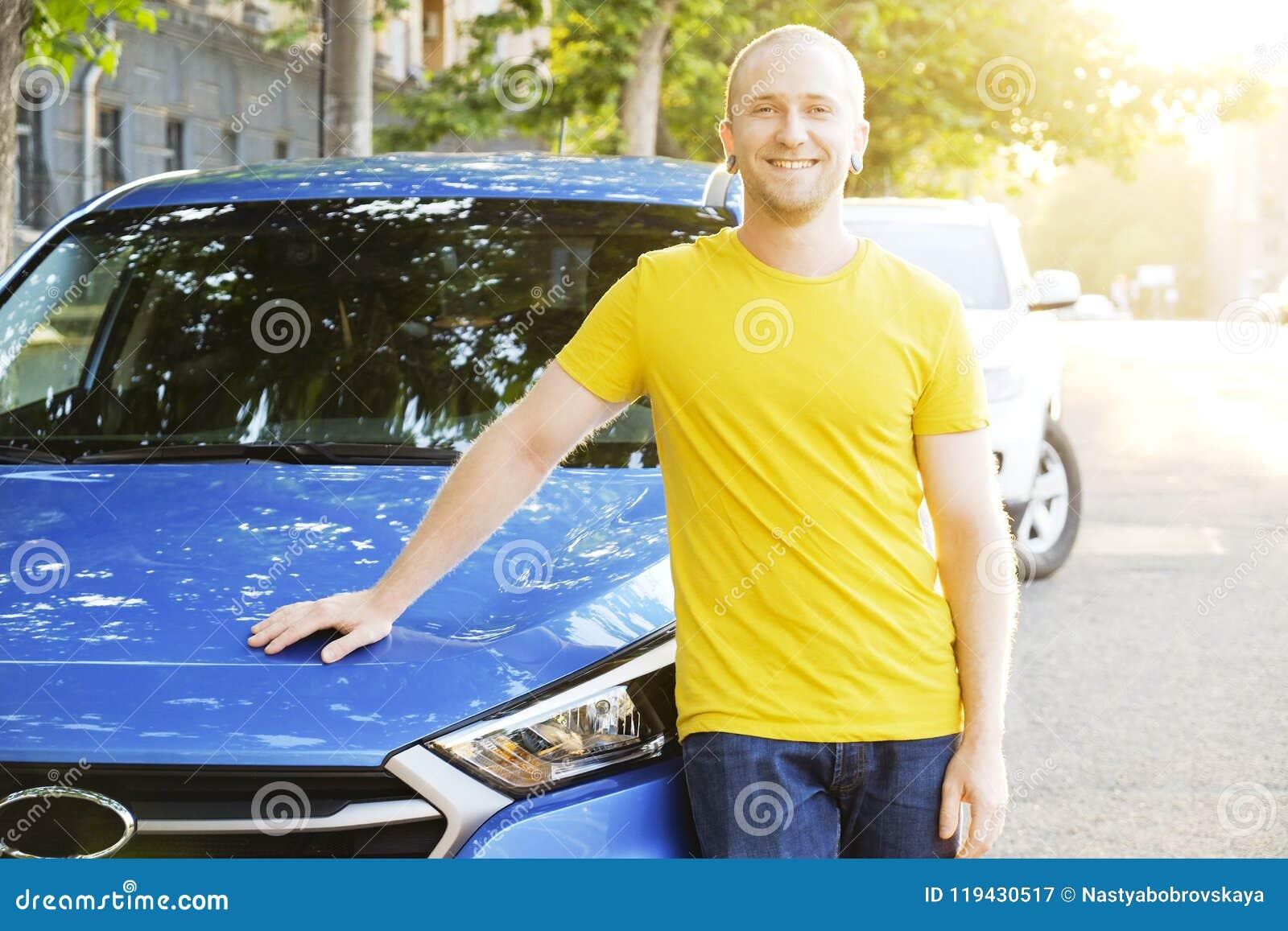 成功的愉快的年轻人和他的汽车在软的日落在urbanistic背景点燃 有车的Busines人在路旁