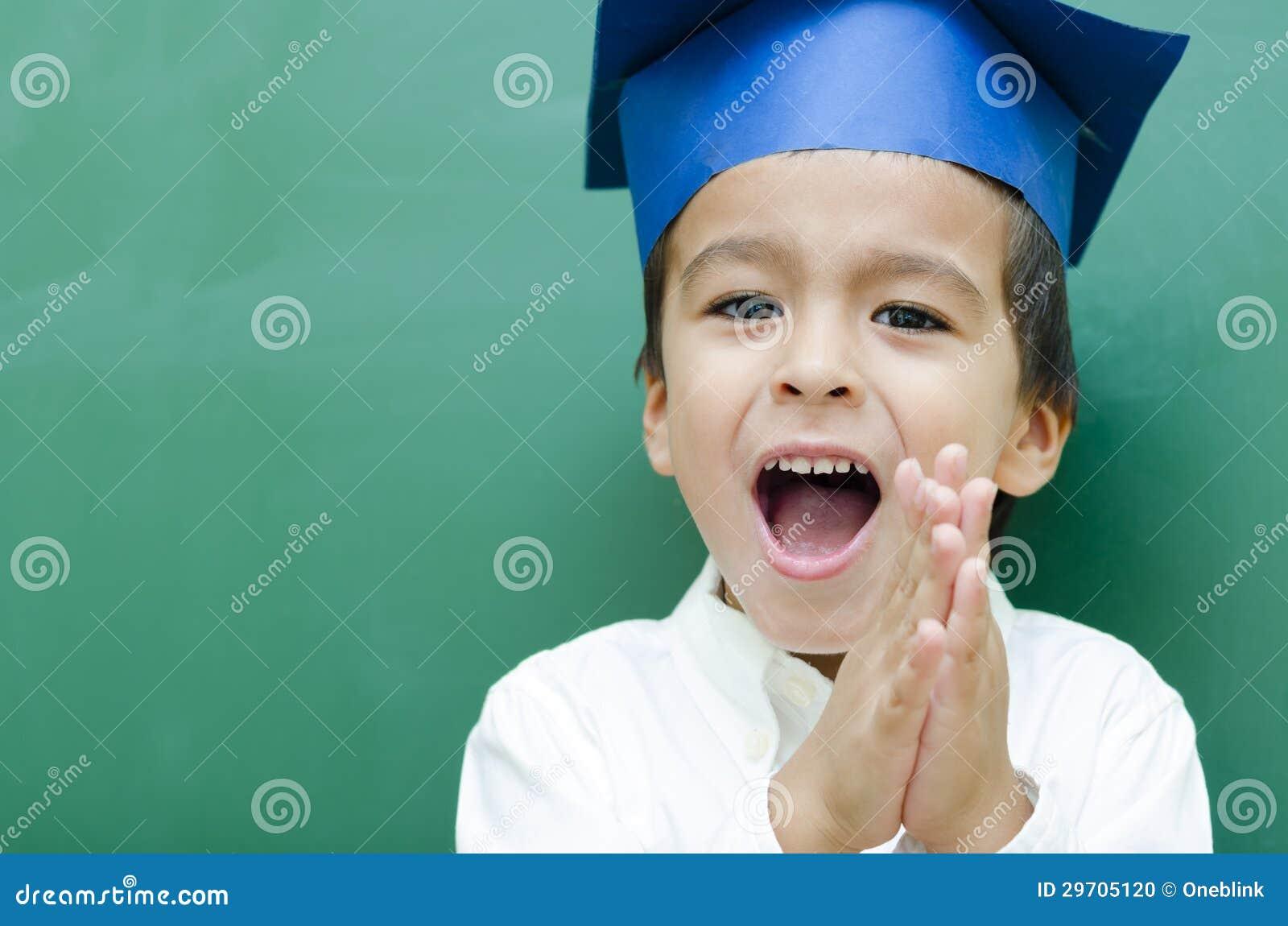 成功的男小学生非常愉快在黑板.图片