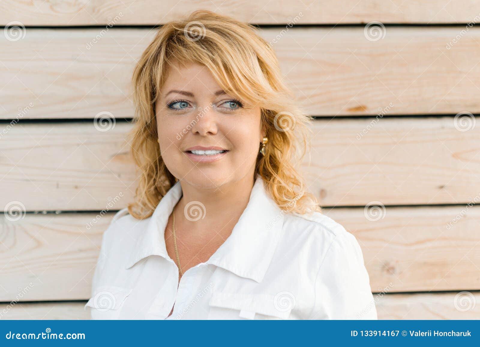 成熟中年白肤金发的妇女特写镜头画象  室外木背景,女性微笑