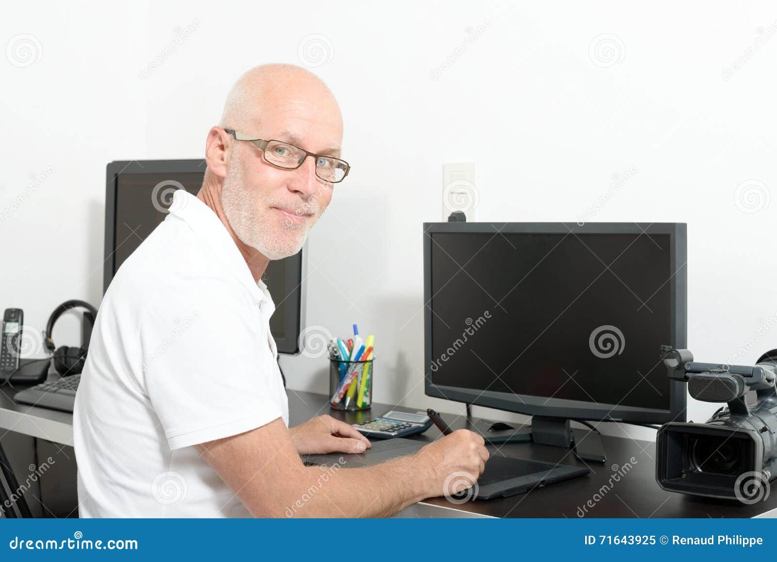 成熟人与他的计算机一起使用