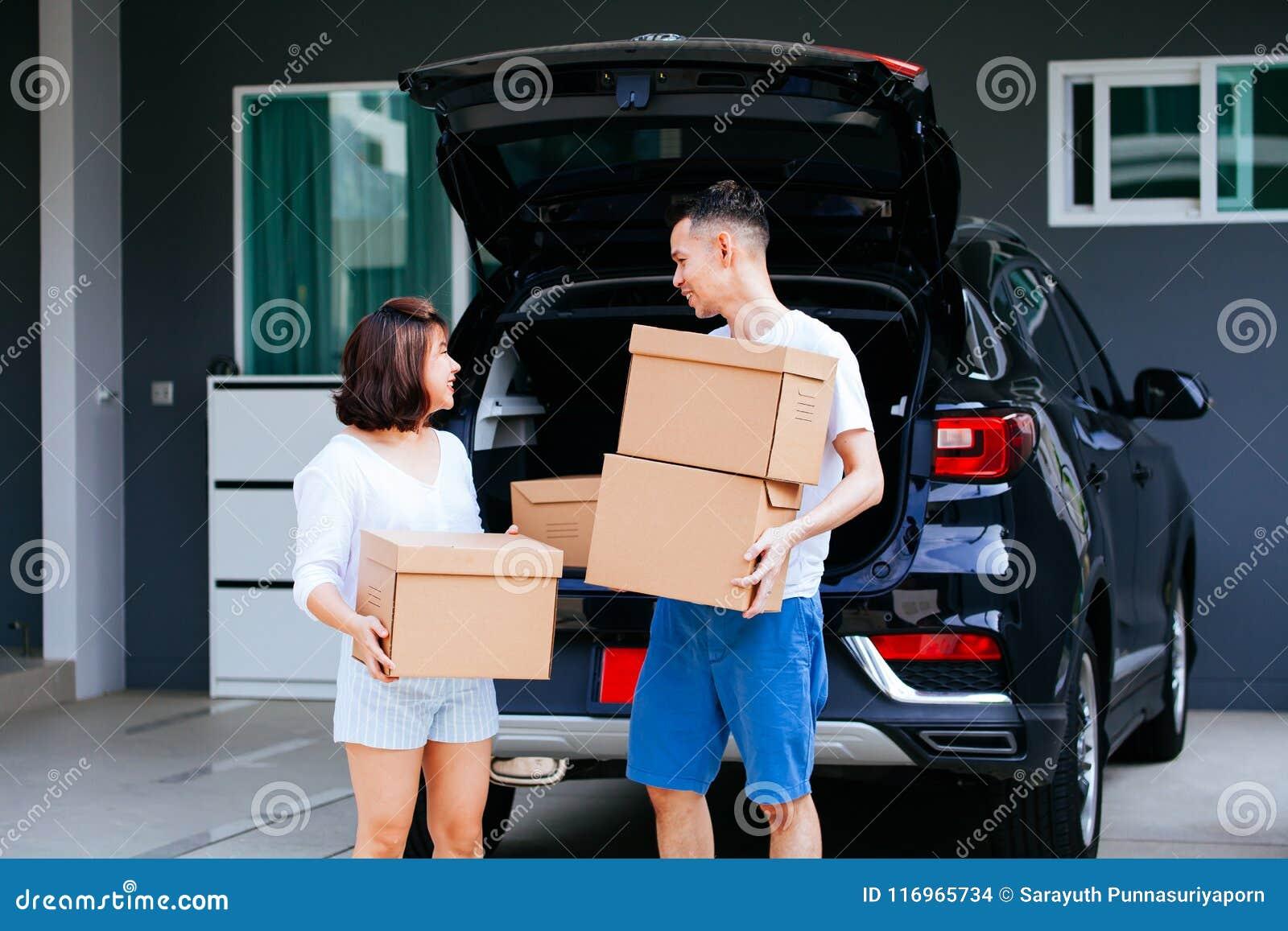 成熟愉快的亚洲人在新的家与从车厢的夫妇运载的纸板箱结婚