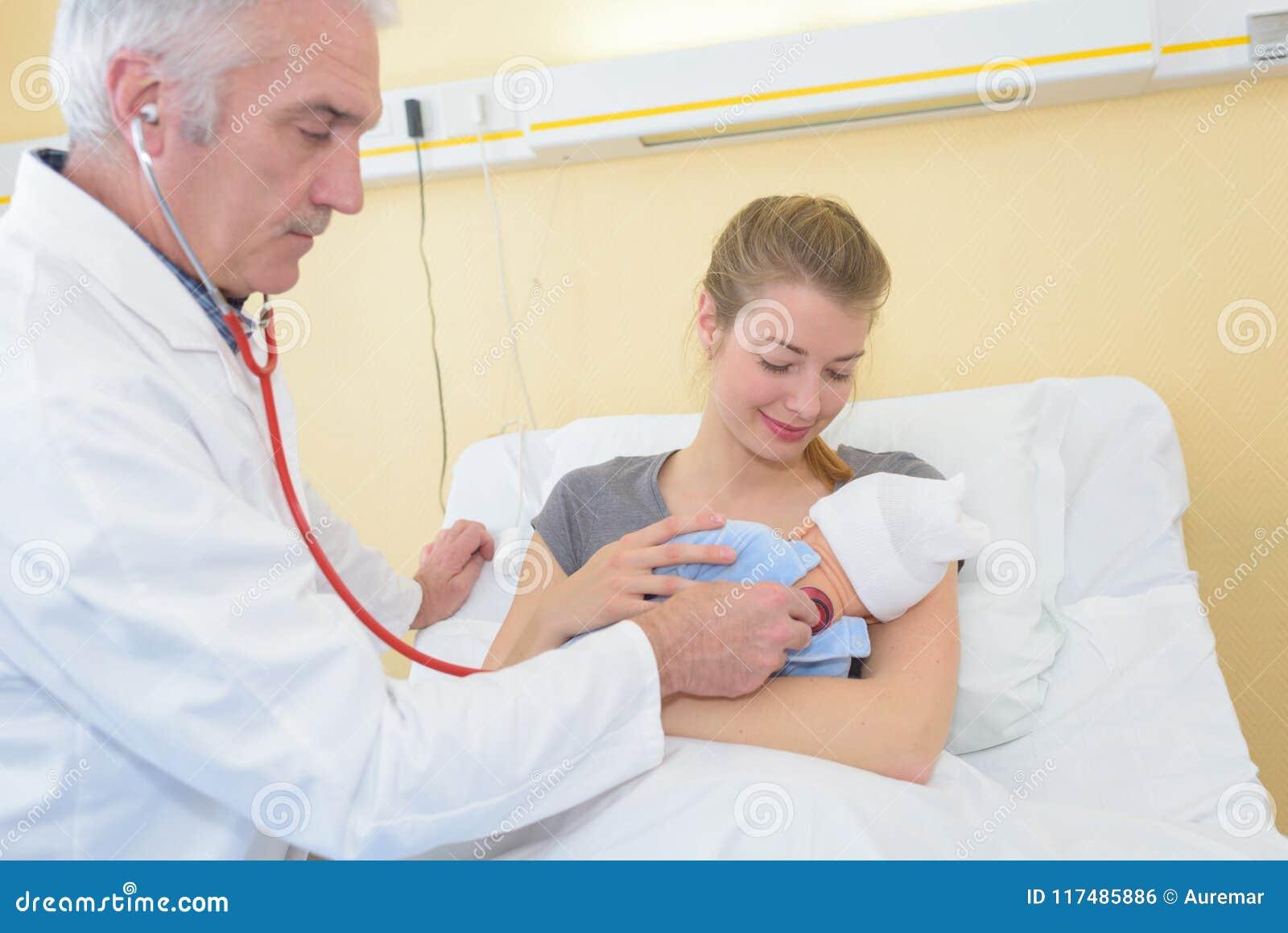 成熟男性有母亲观看的医生审查的女婴
