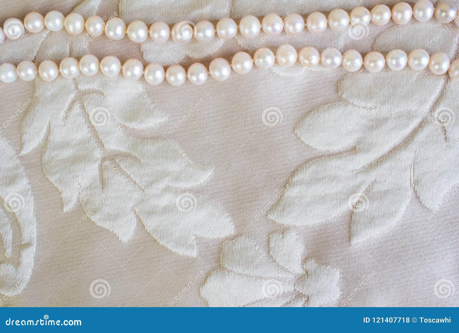 成珠状在缎织品纹理背景的项链与空间为