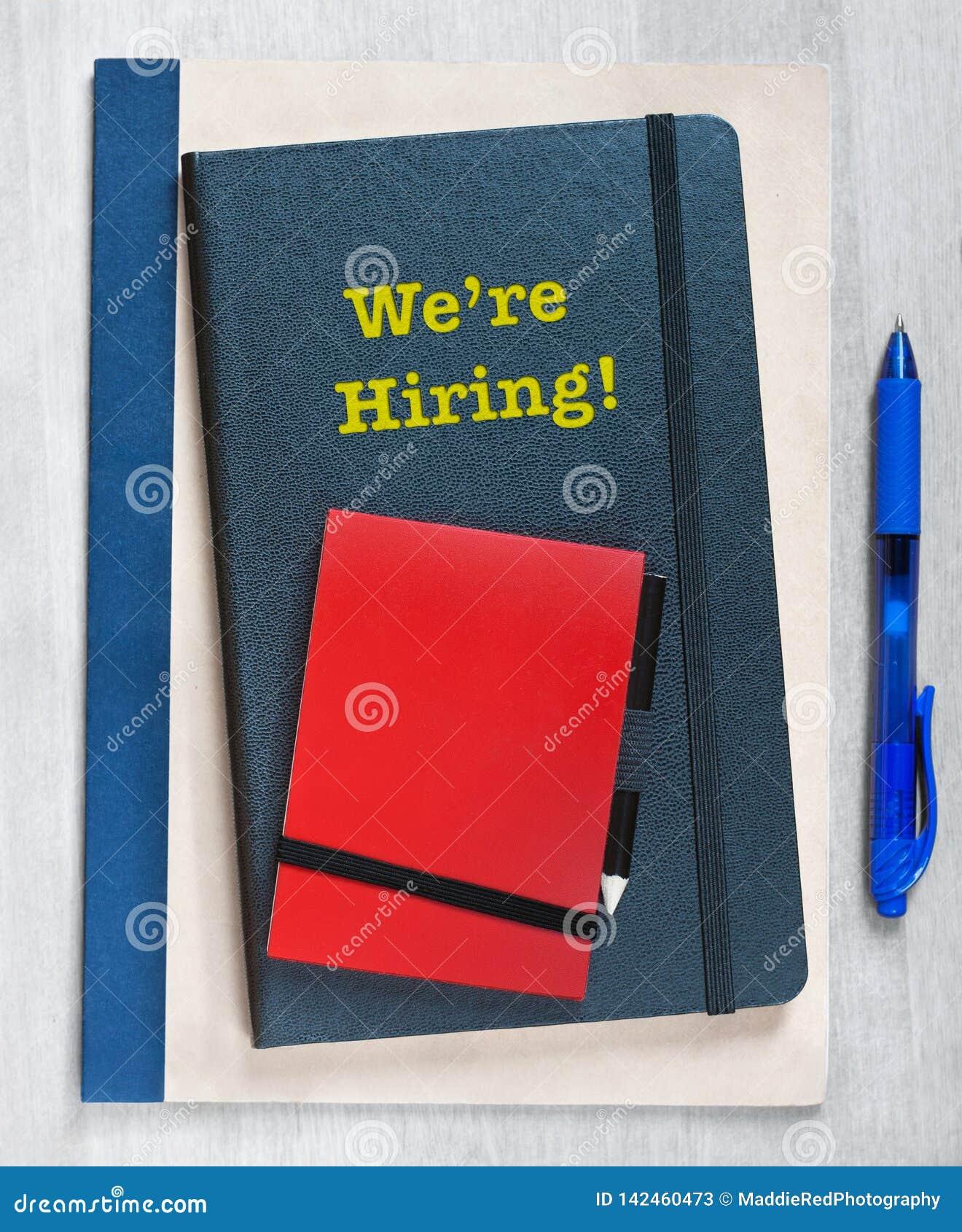 我们聘用!在堆写的文本笔记本,在木背景的一支蓝色笔旁边