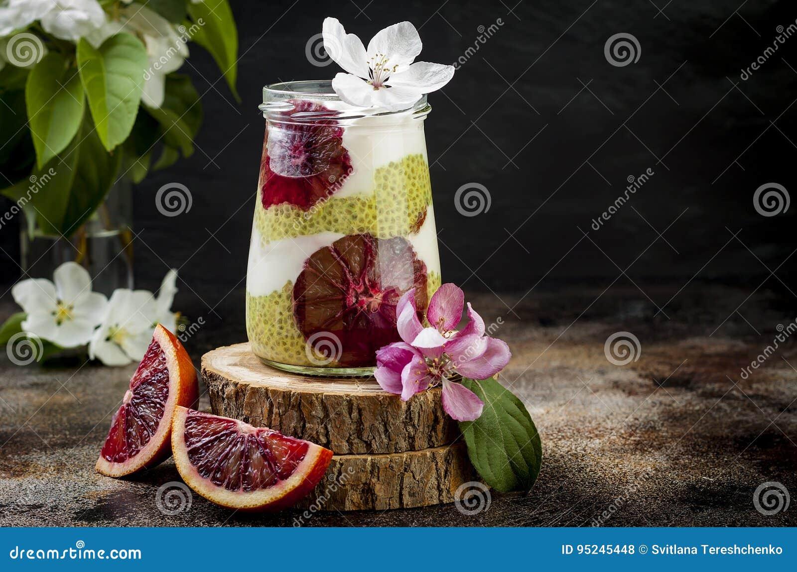 戒毒所分层了堆积matcha绿茶chia种子布丁用血橙 素食主义者点心用椰子鞭打了奶油