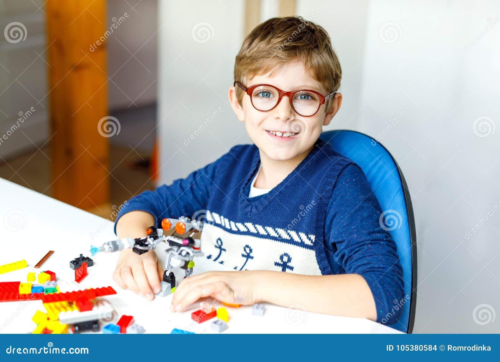 戴使用与许多的眼睛眼镜的小白肤金发的孩子五颜六色的塑料块