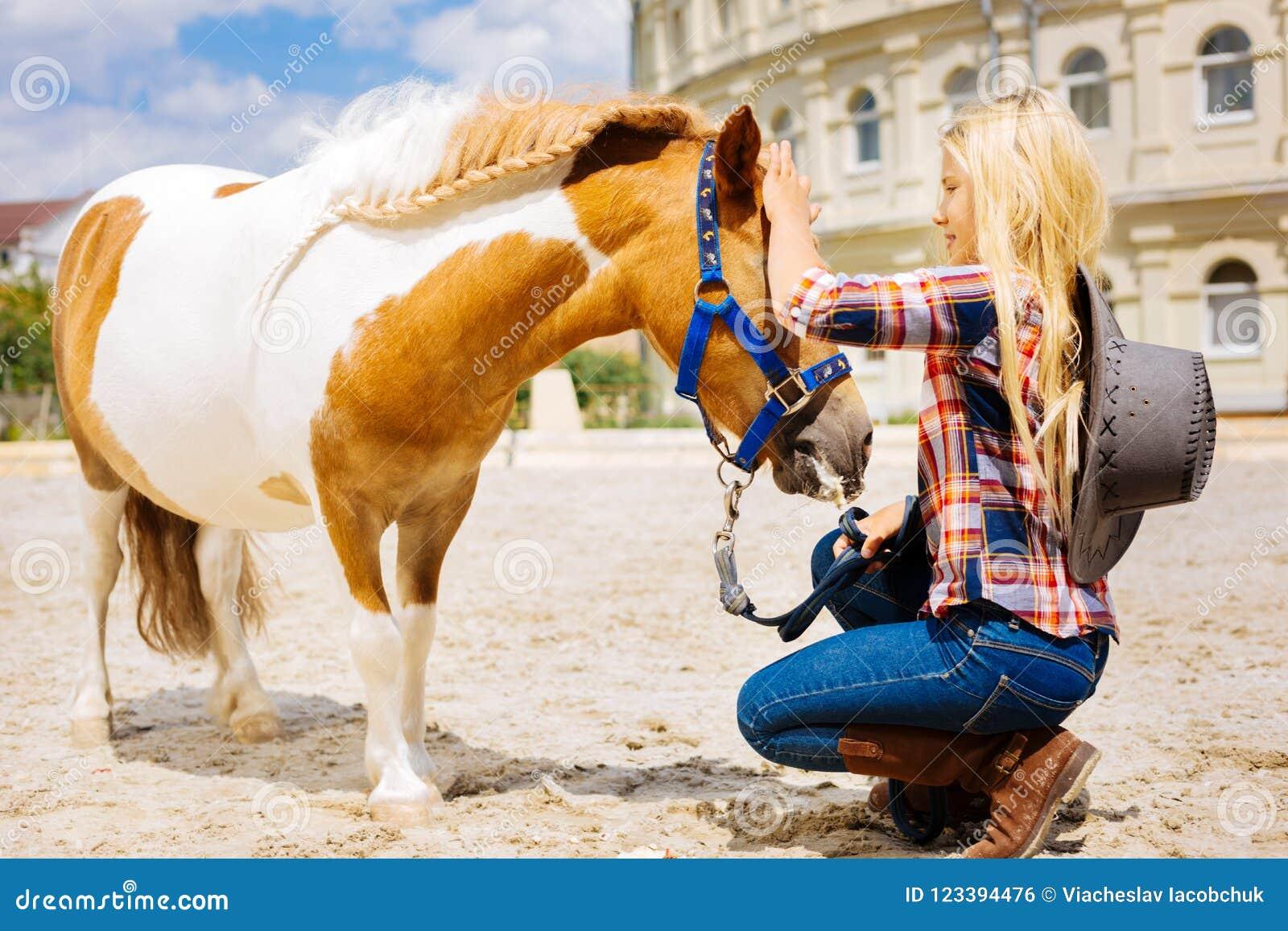 戴时髦的帽子的牛仔女孩来到小的逗人喜爱的马