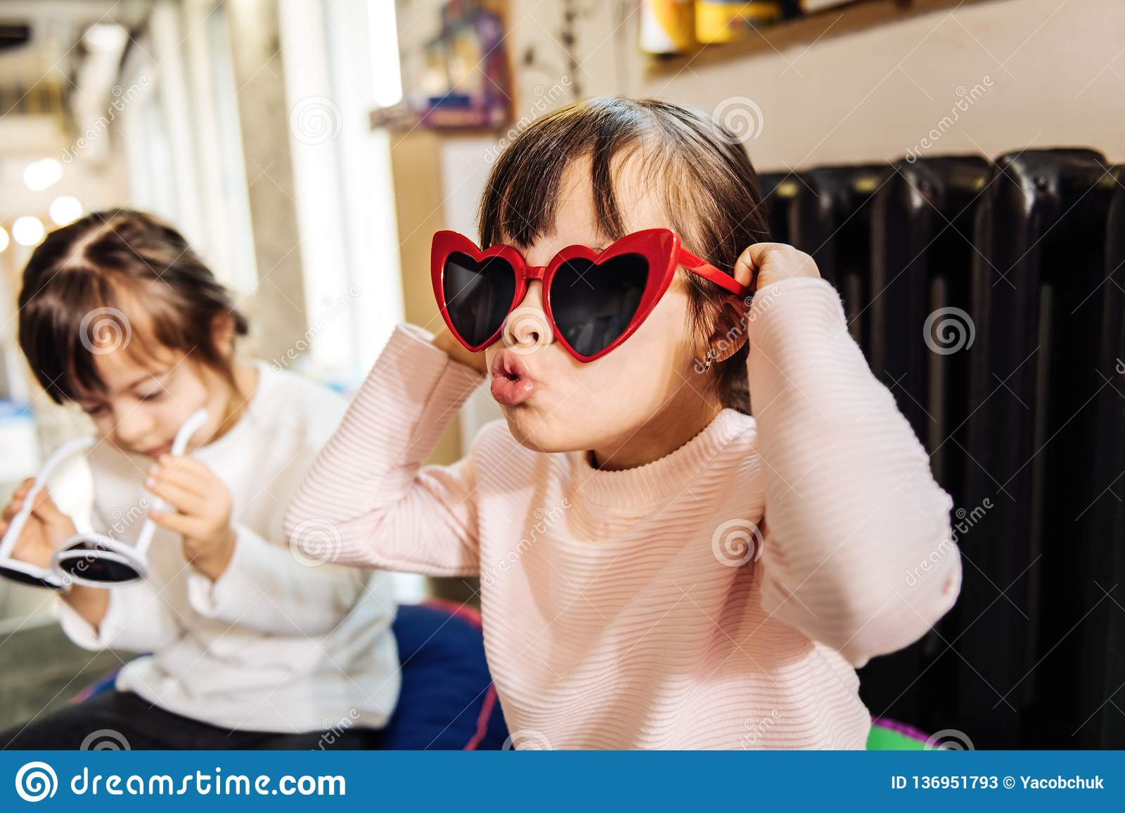 戴明亮的红色太阳镜的逗人喜爱的滑稽的深色头发的女孩