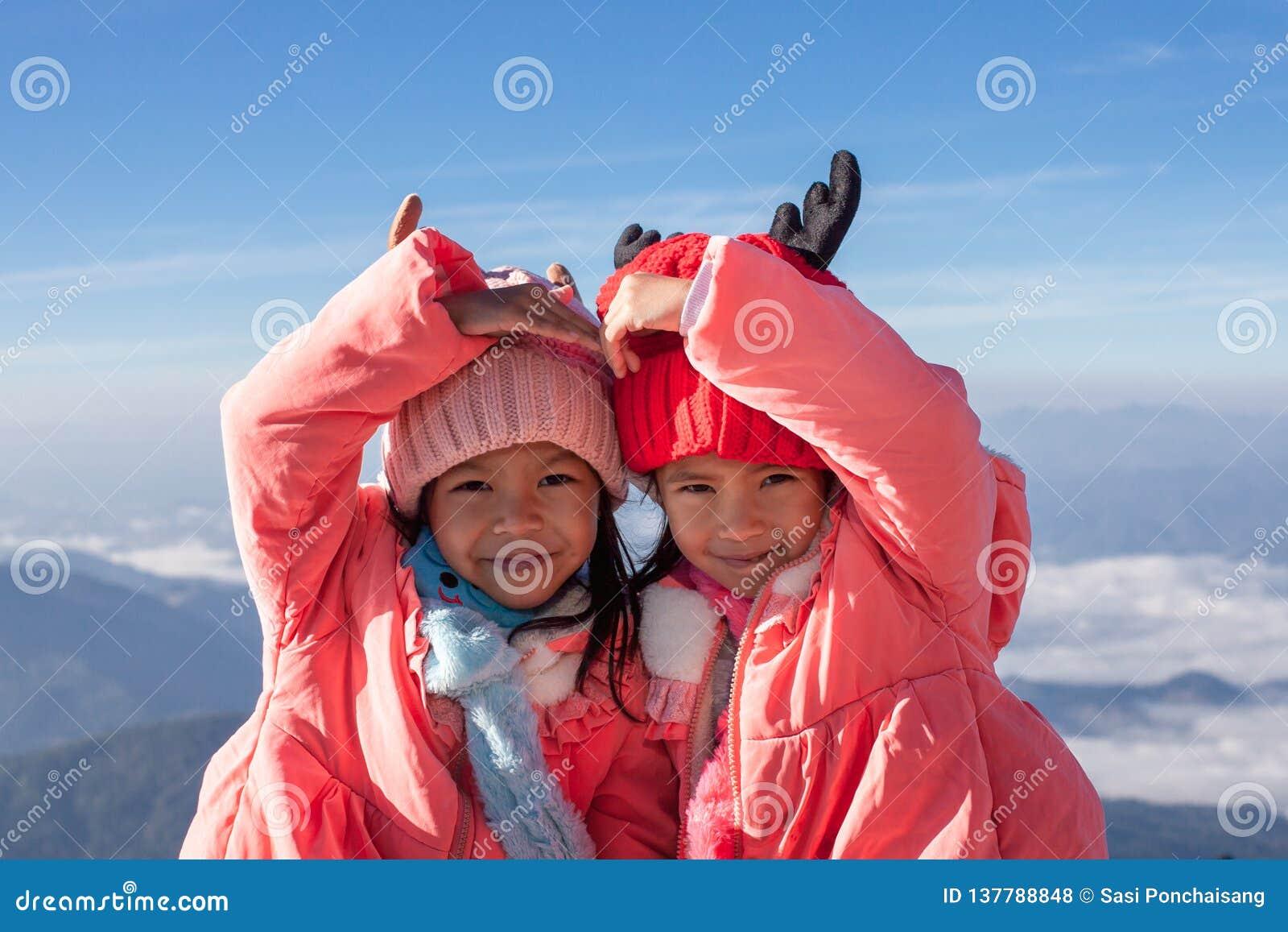 戴毛线衣和温暖的帽子的两个亚裔儿童女孩做心脏与爱一起在美丽的薄雾和山