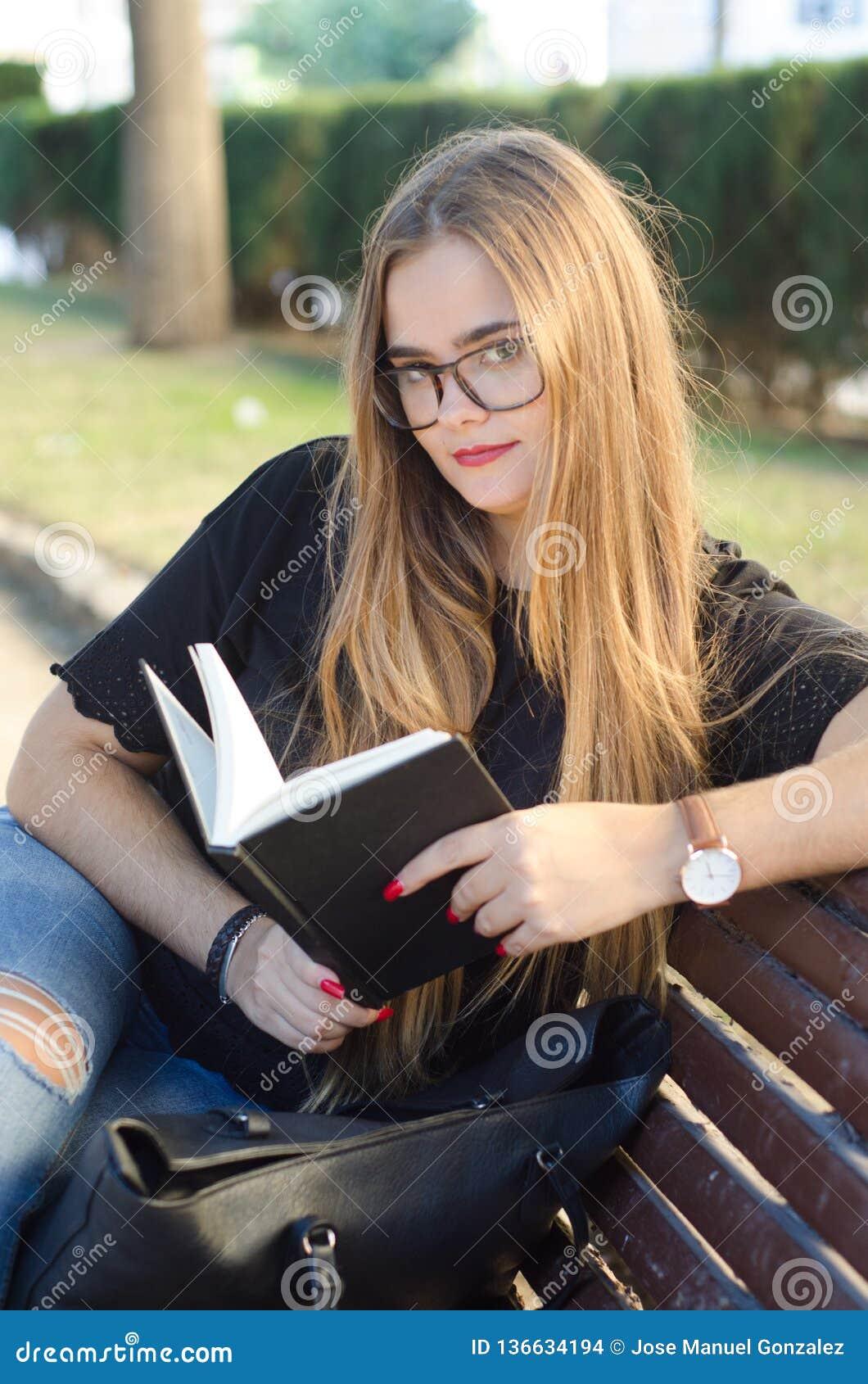 戴看对您和读在公园长椅的眼镜的甜白肤金发的女孩一本书