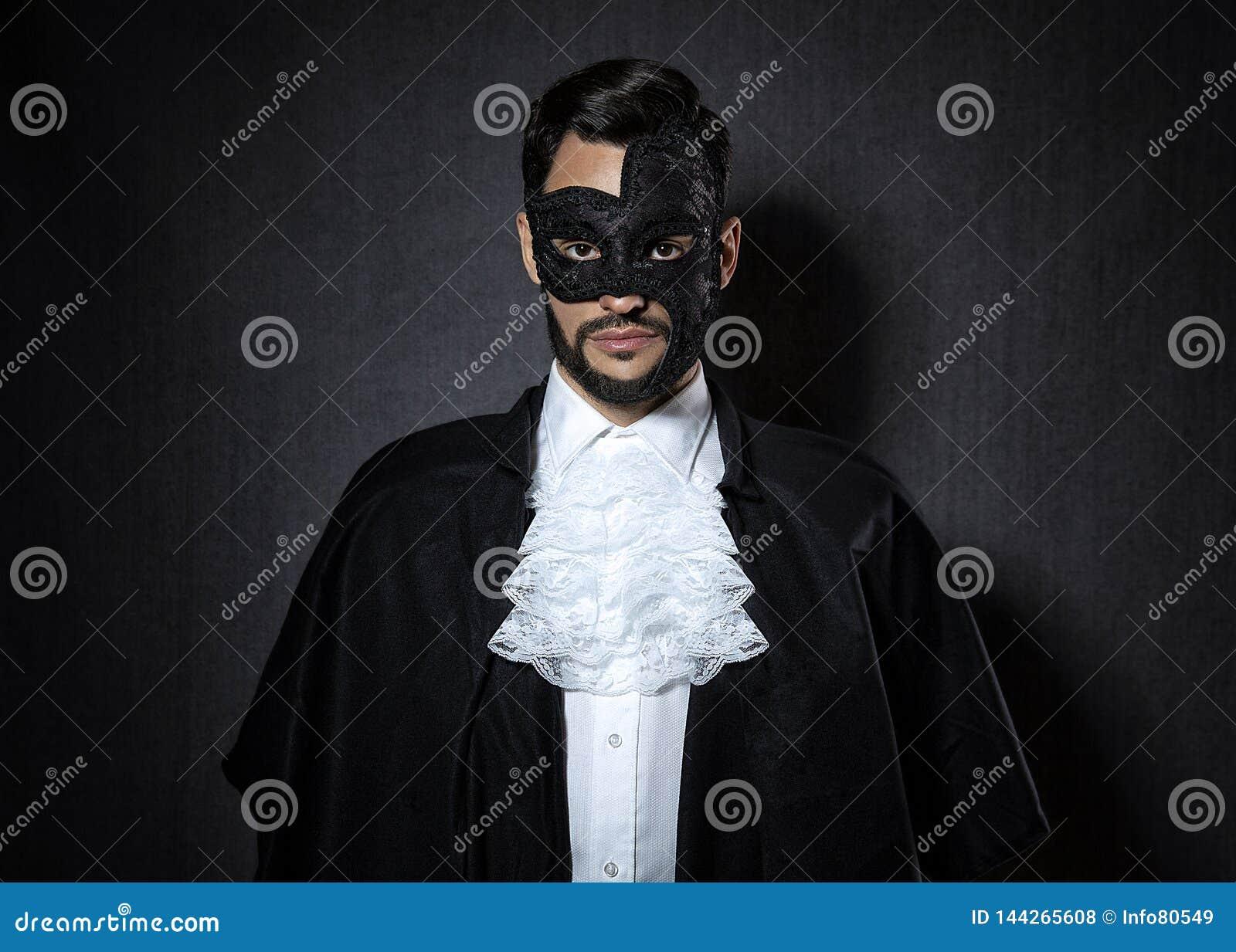 戴着一个黑暗的面具的年轻人,穿戴在歌剧神色的幽灵