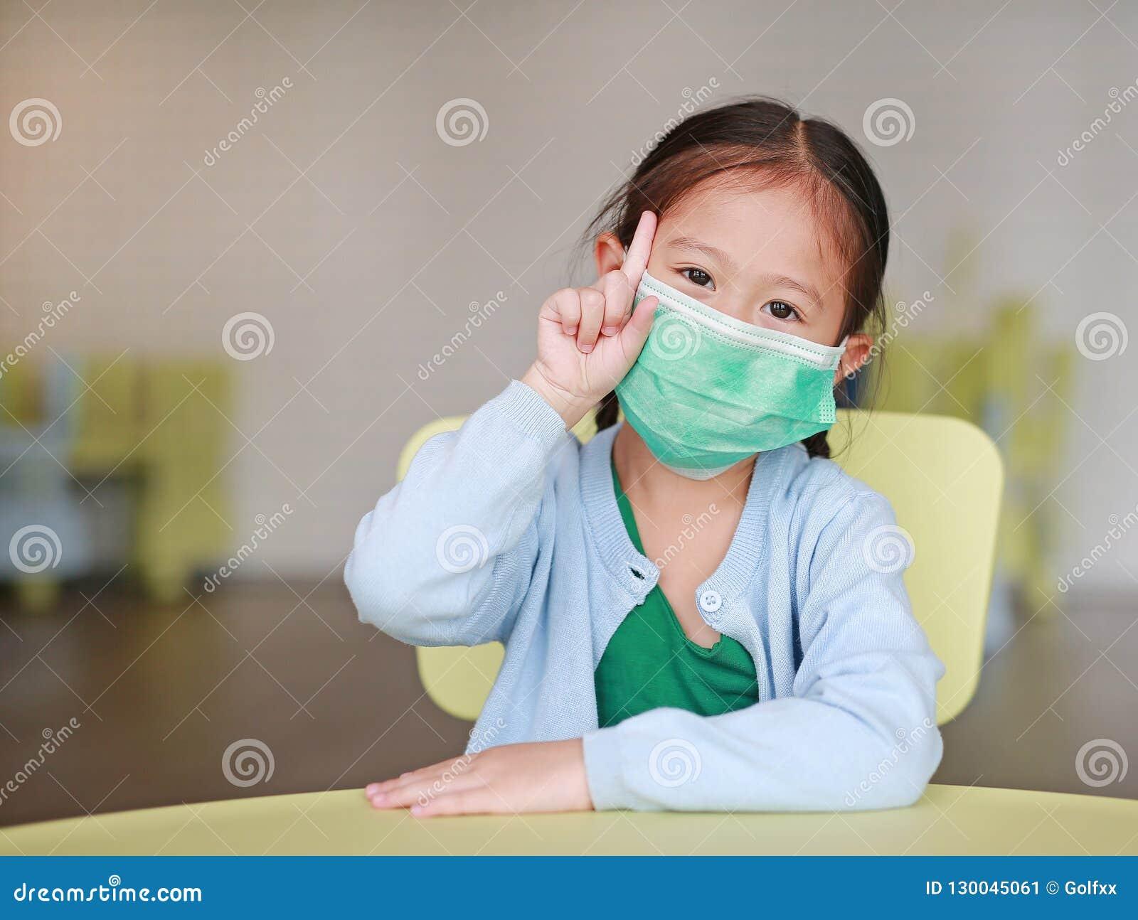 戴着与陈列一食指的逗人喜爱的矮小的亚裔儿童女孩一个防毒面具坐孩子椅子在儿童居室