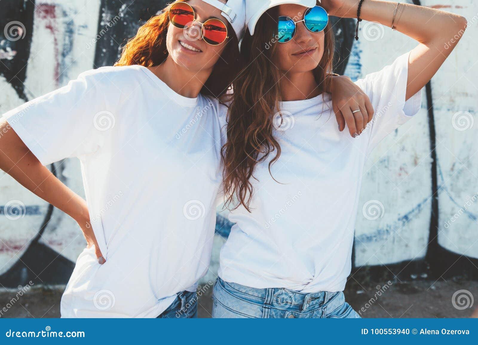 戴简单的T恤杉和太阳镜的模型摆在街道wa