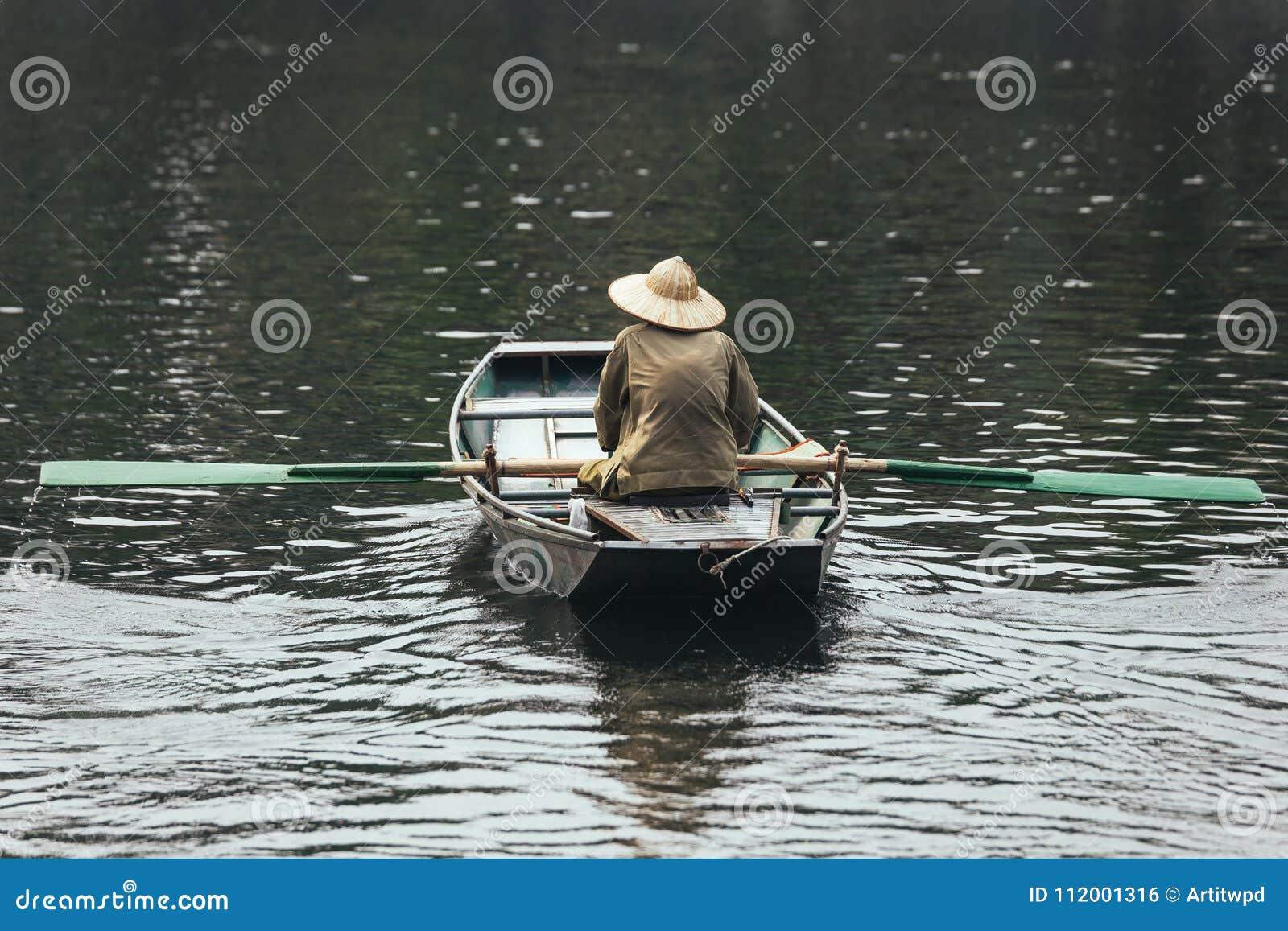 戴绿色衬衣和圆锥形帽子的划艇人坐在有桨的一条小船在河在背景中