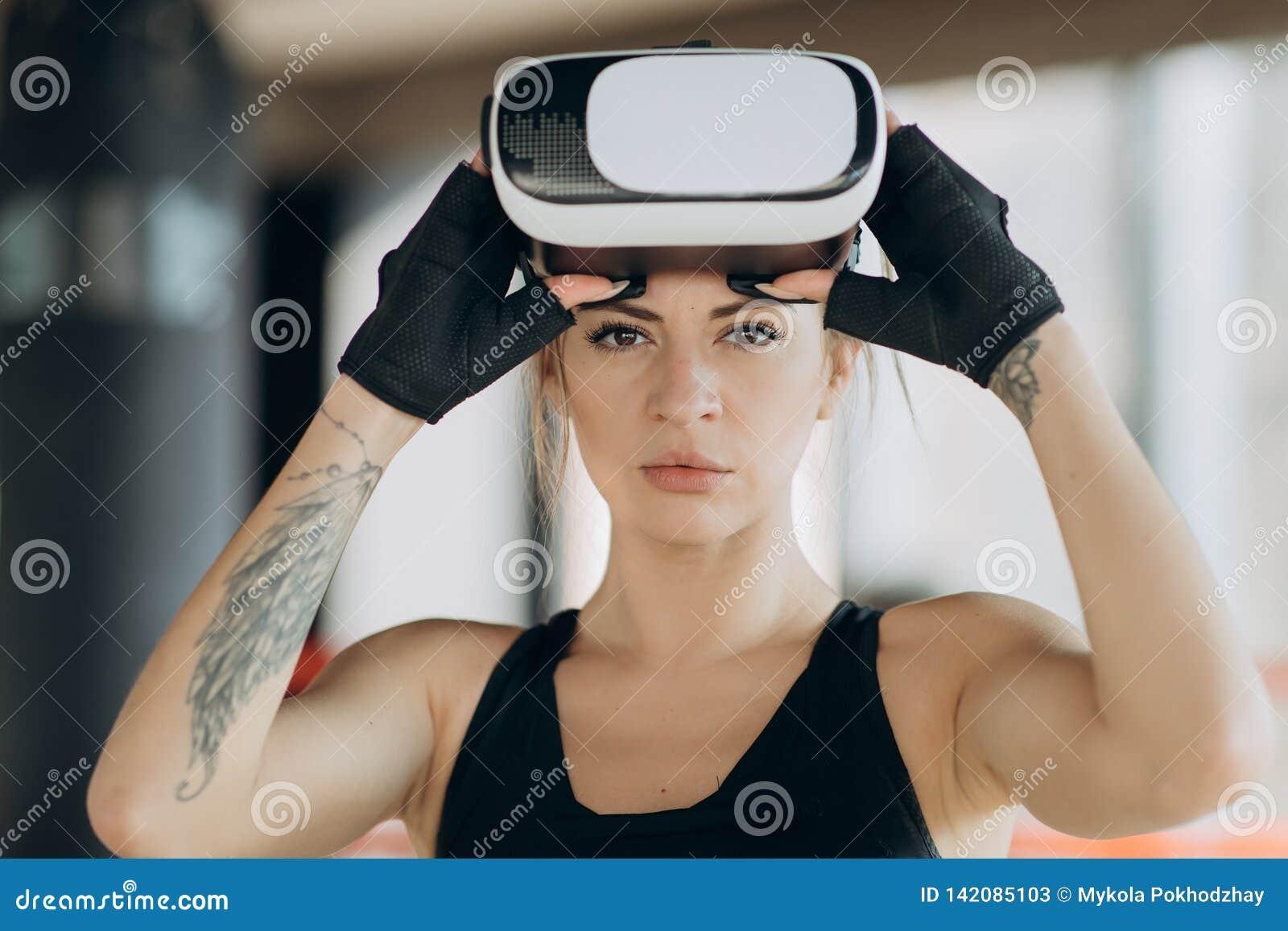 戴被增添的现实眼镜的游戏玩家站立在演奏行动模拟器比赛流动应用程序的拳击姿态,女性