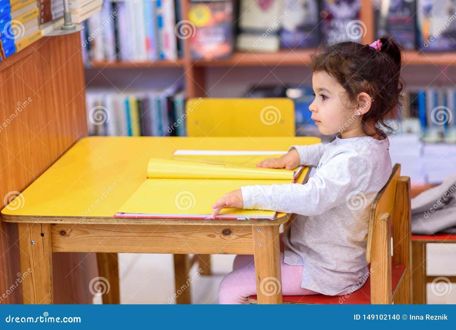 户内女孩在书前面 逗人喜爱的年轻小孩坐椅子在表和看书附近