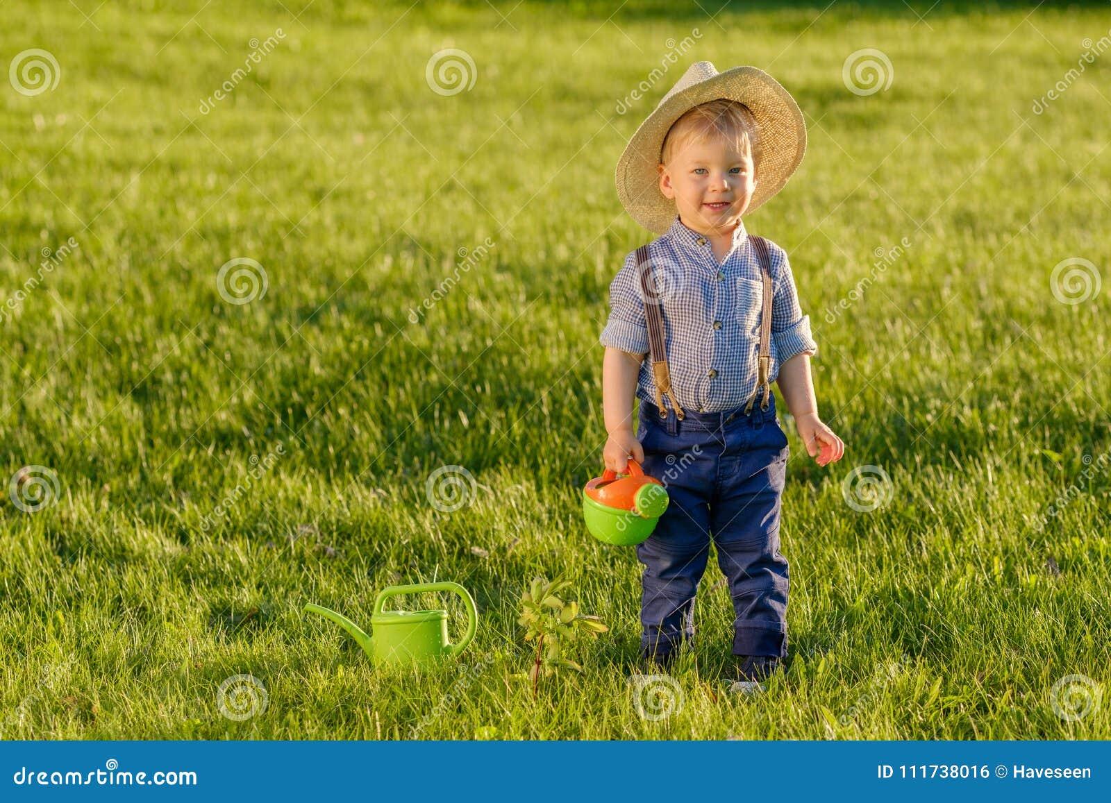 户外小孩孩子 使用喷壶的一个岁男婴佩带的草帽