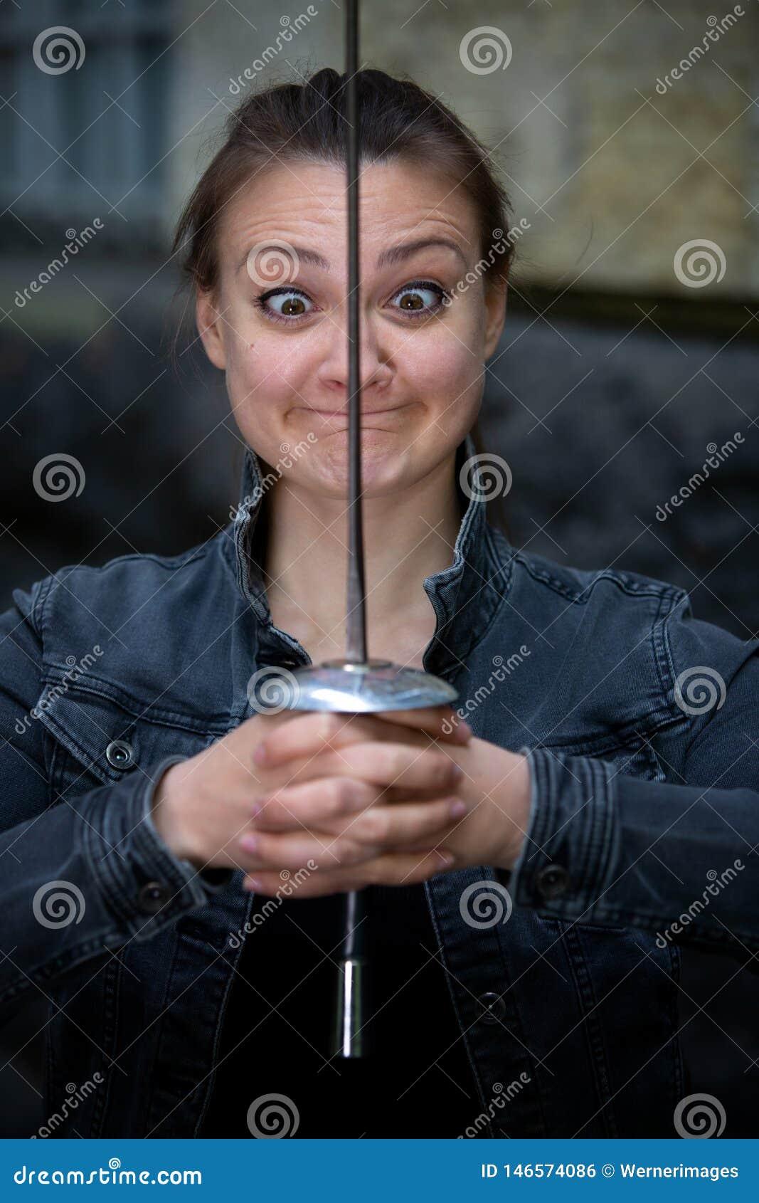户外年轻深色的斗眼的妇女与锐剑