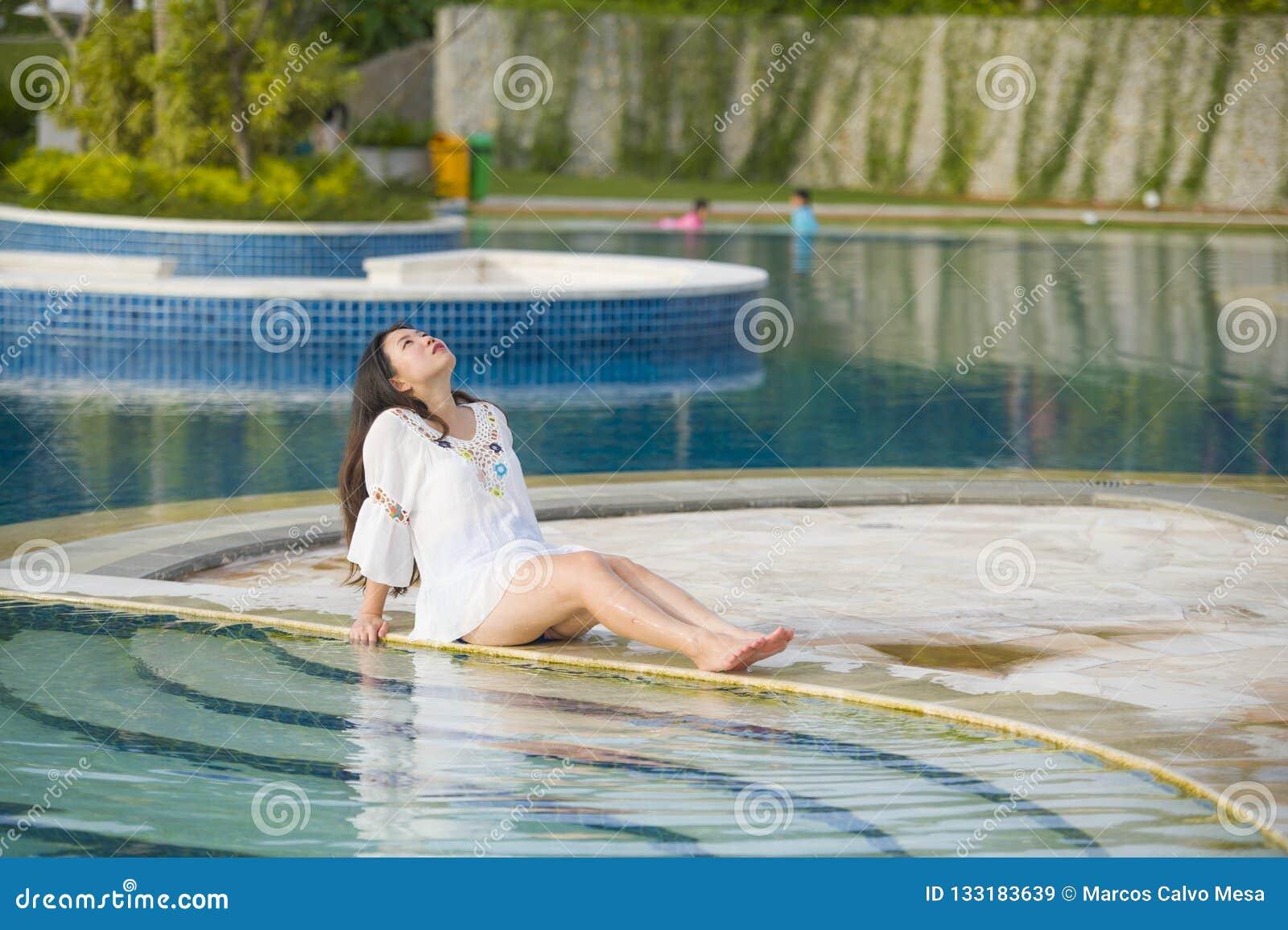 户外放松在热带手段游泳场的年轻愉快和美丽的亚裔韩国旅游妇女生活方式画象