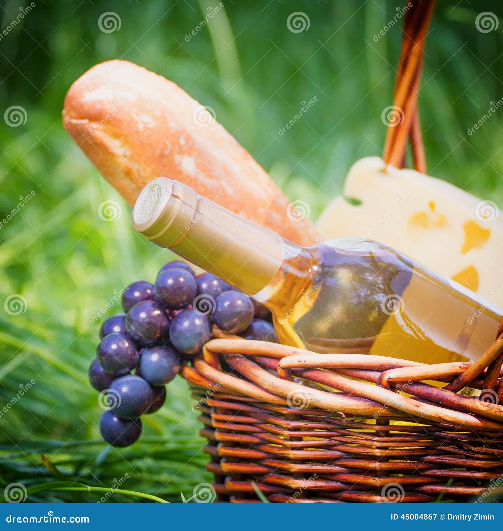 瓶在篮子的白葡萄酒用户外野餐的新鲜食品.