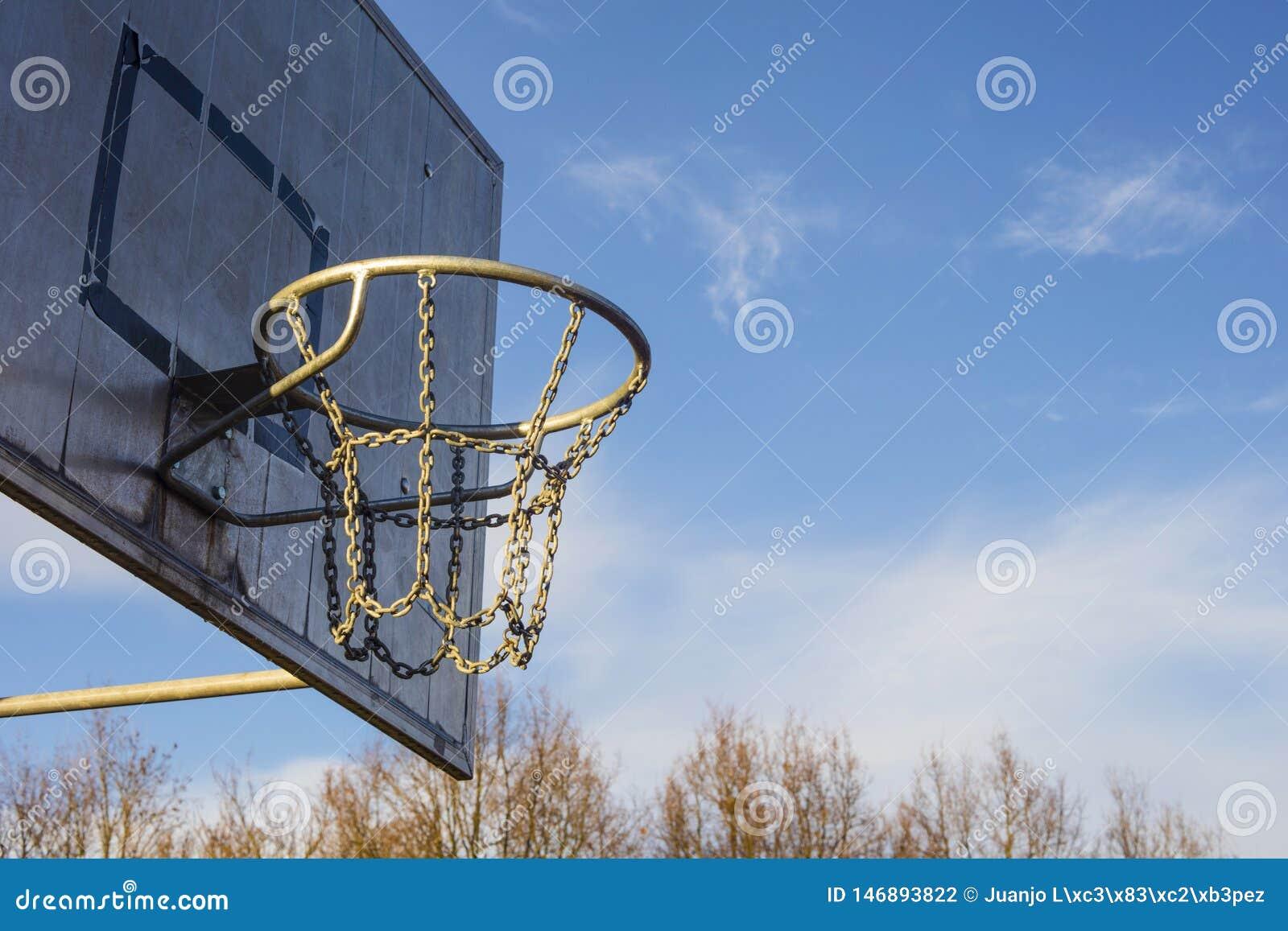 户外金黄篮球篮子细节在日落天空蔚蓝