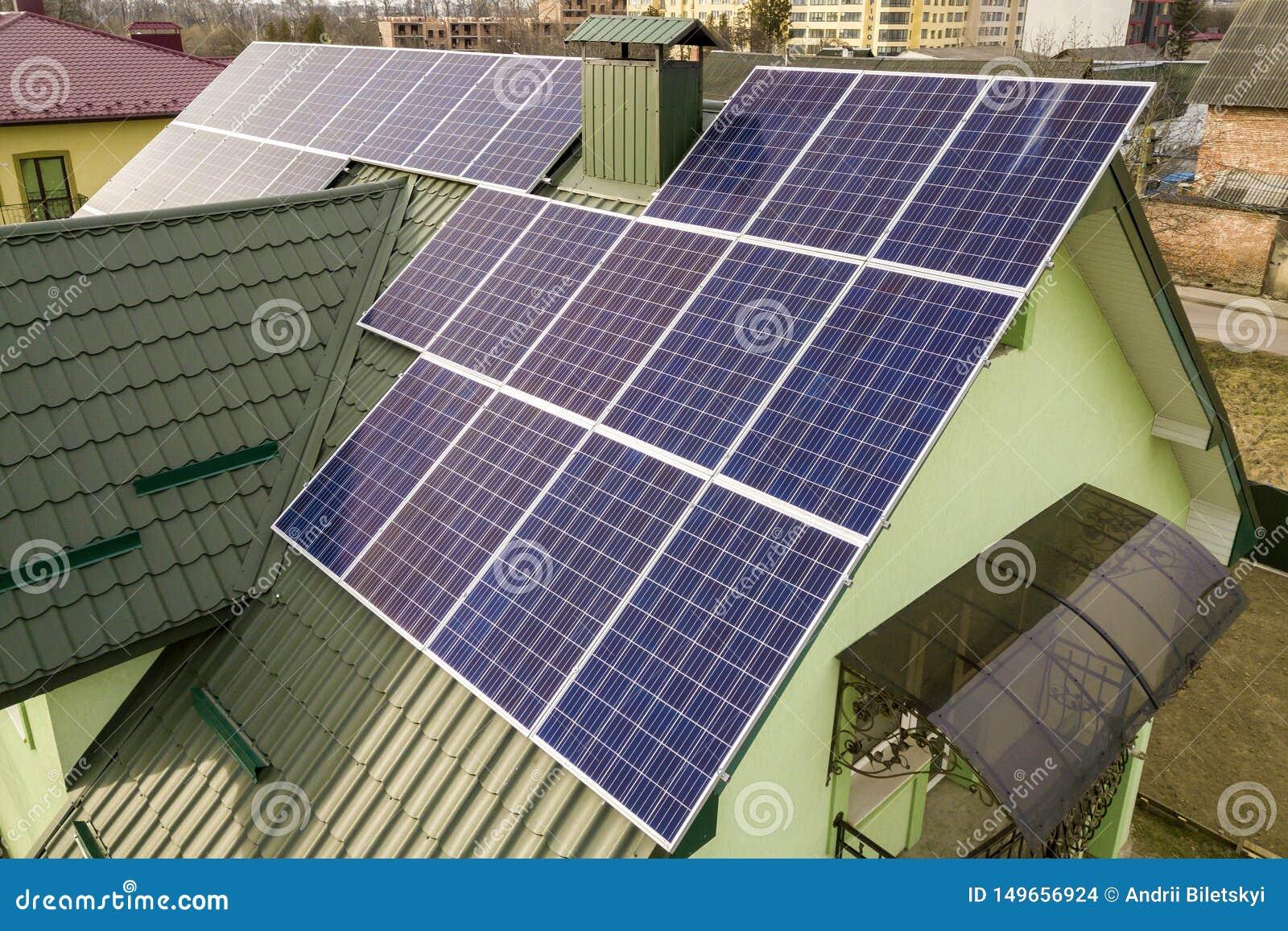 房子村庄鸟瞰图与蓝色发光的太阳照片流电盘区系统的在屋顶 可更新的生态绿色能量