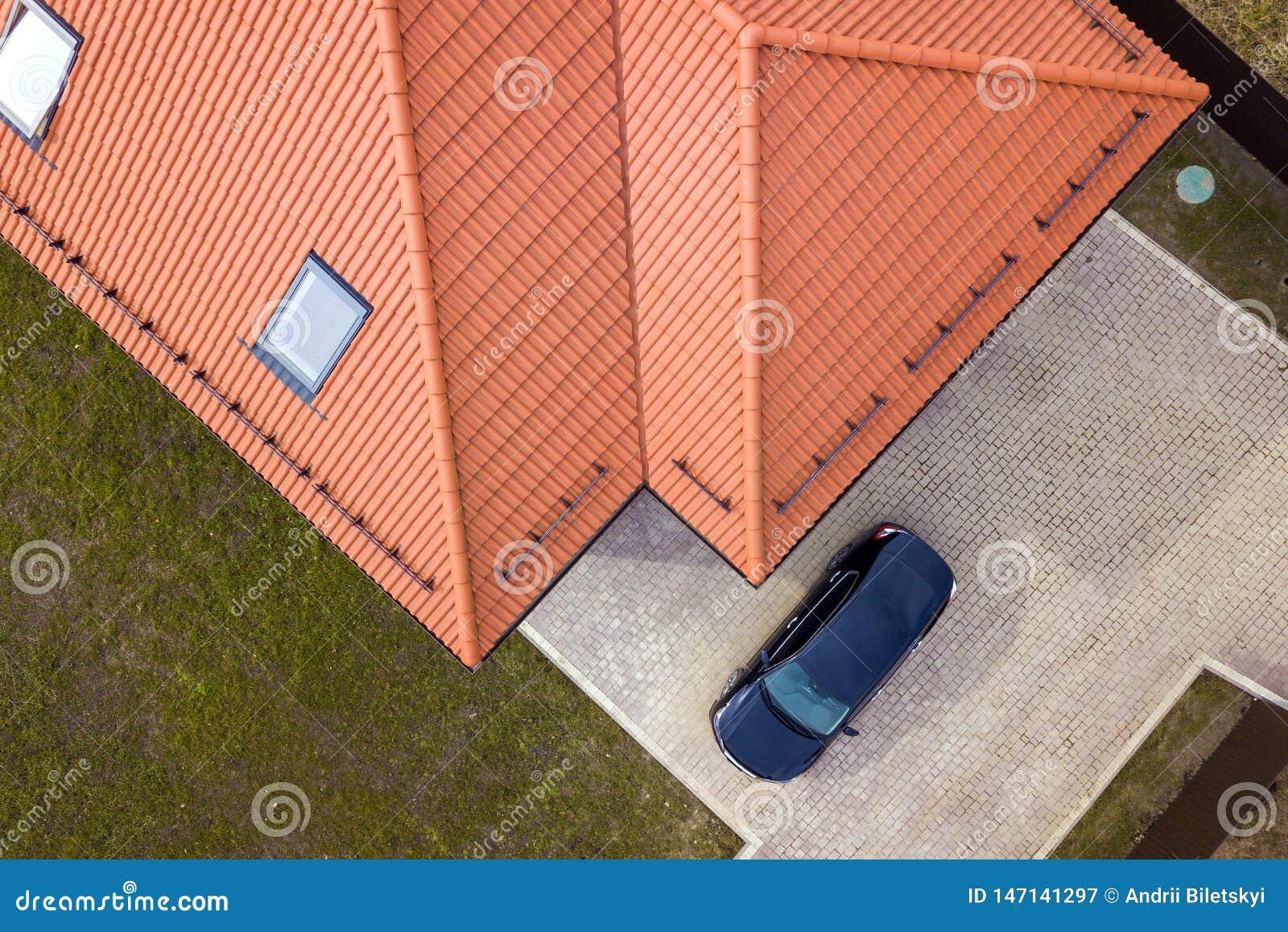 房子金属有顶楼窗口和黑汽车的木瓦屋顶空中顶视图在被铺的围场