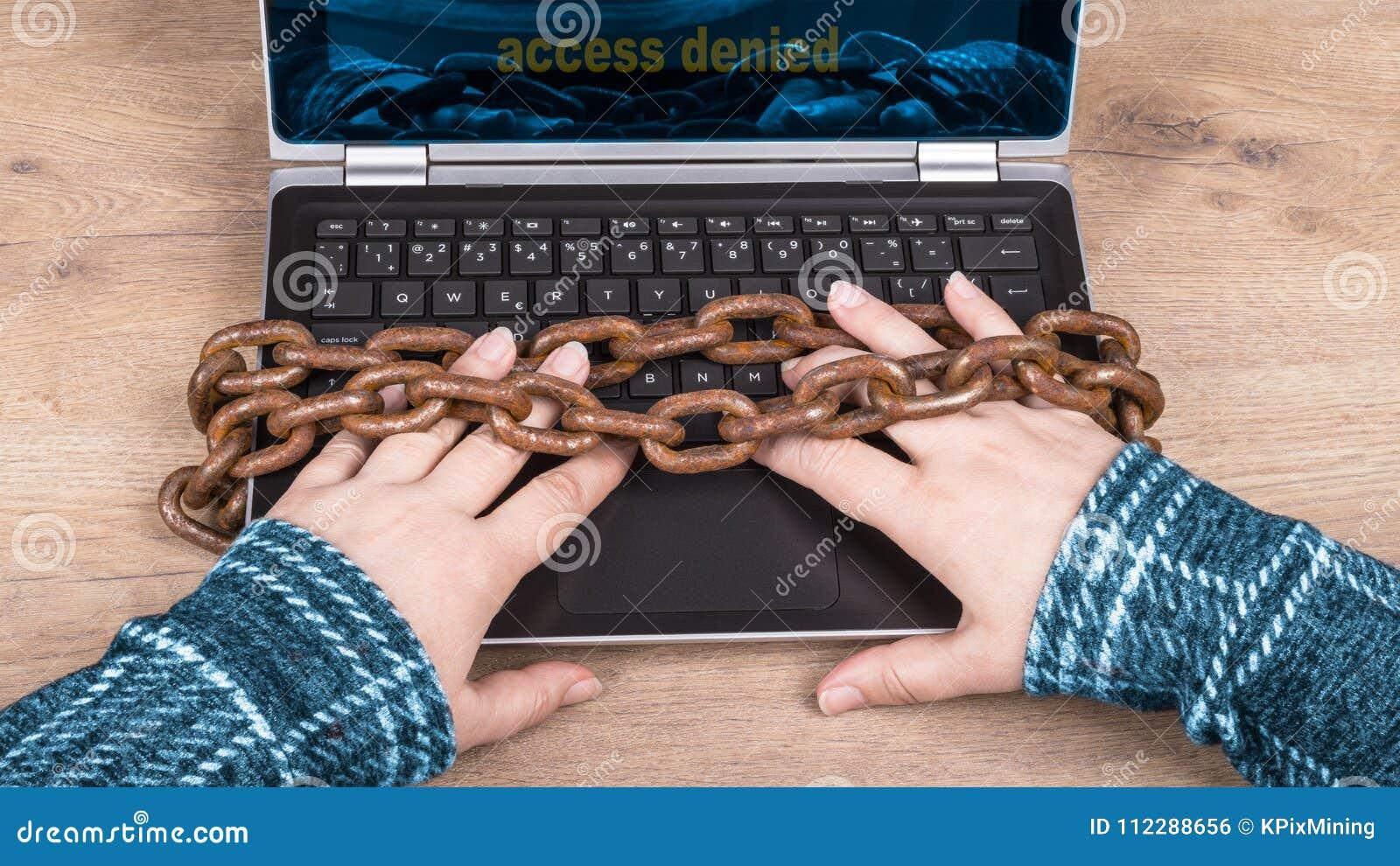 手、膝上型计算机键盘和老生锈的链子特写镜头在木背景