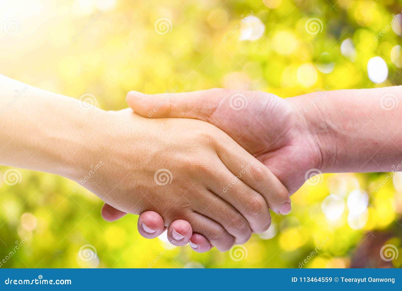 手人握手在绿色bokeh背景的