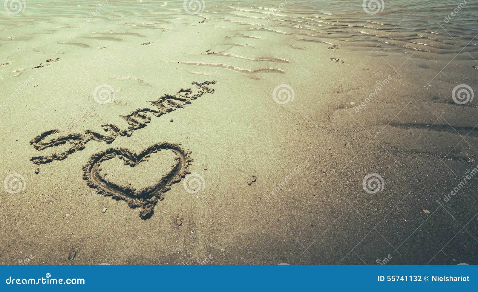 手写的夏天在海滩的沙子与可爱的心脏的