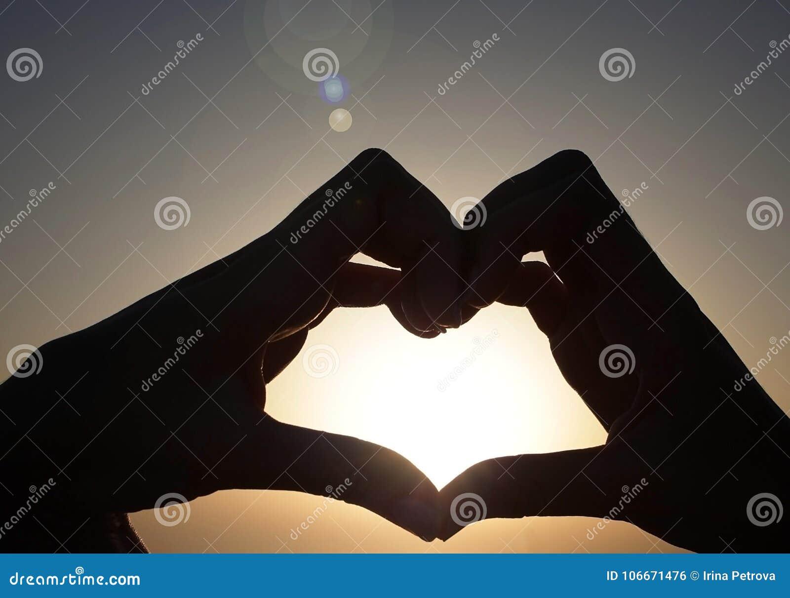 手剪影在爱的在日落天空