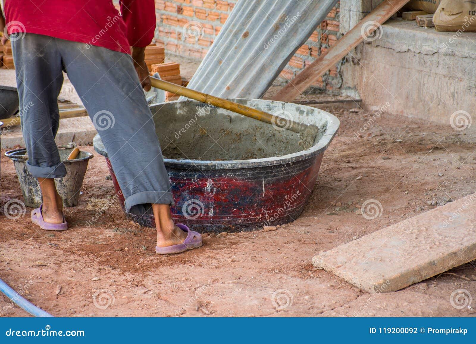 手动地混合在搅拌器盘子的建筑工人混凝土