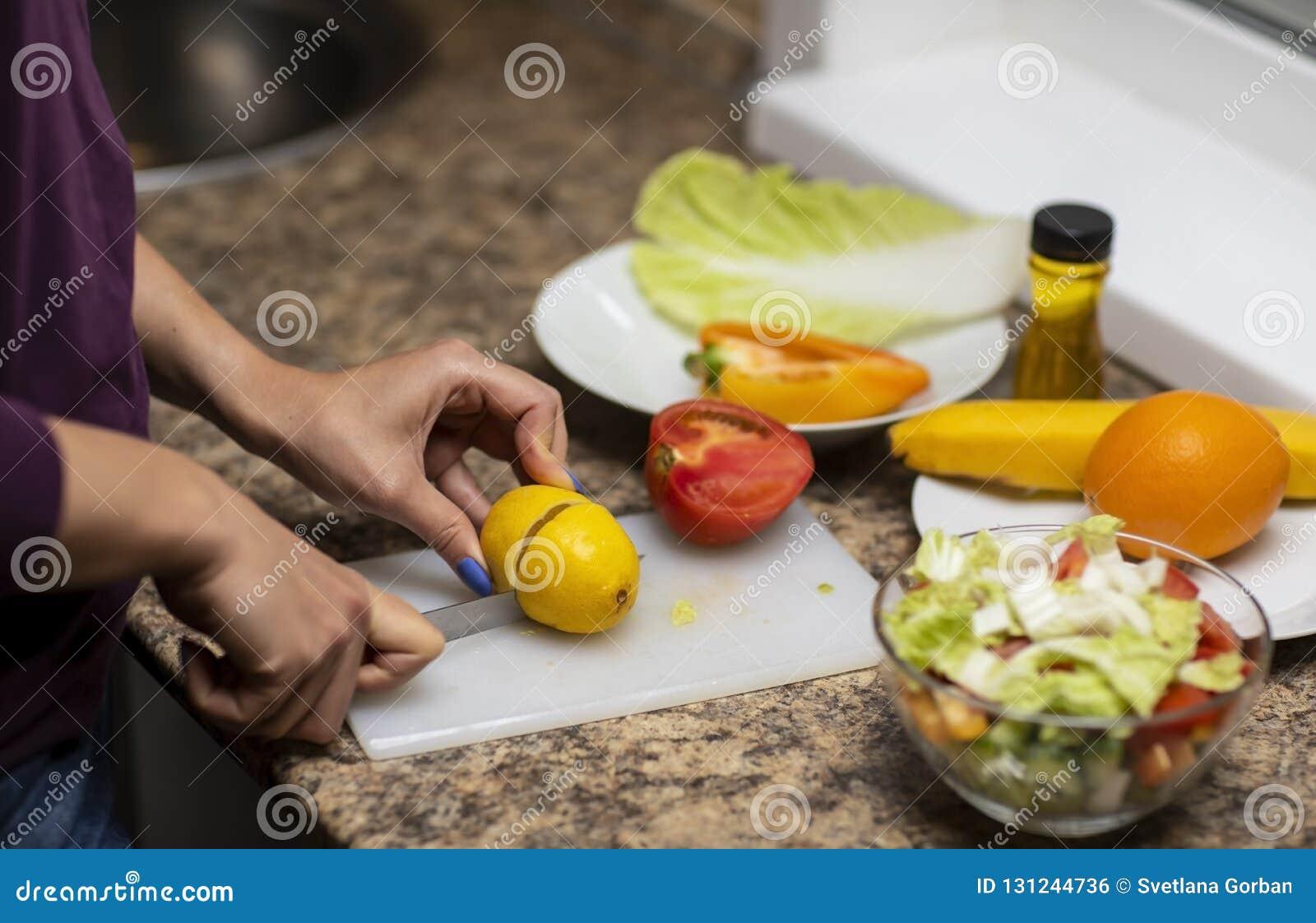 手在厨房里切开沙拉的菜