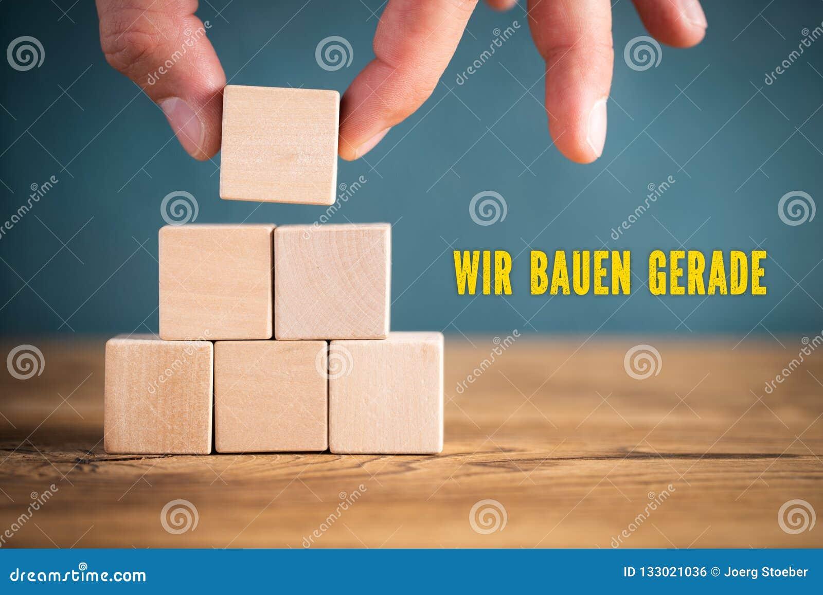 手堆积空白的立方体和消息'建设中'用德语