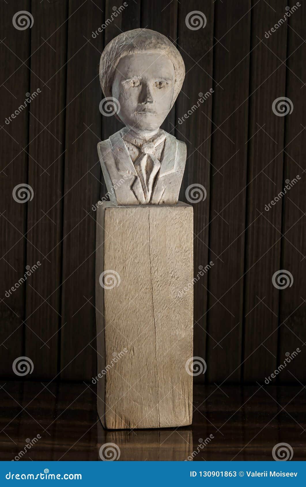 手工制造木小雕象,一个人的雕象一条领带的,在黑暗的木头背景