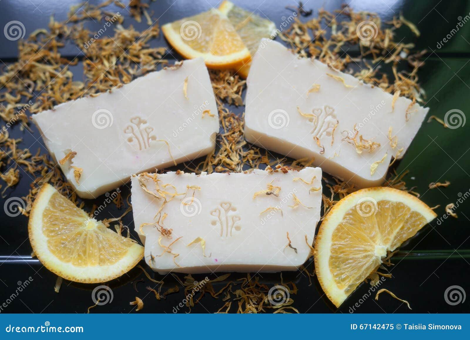 在万寿菊的瓣的手工制造肥皂用在黑暗的背景的桔子.图片