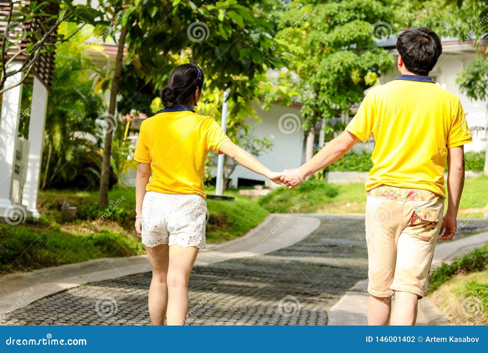 手拉手走在公园的夫妇