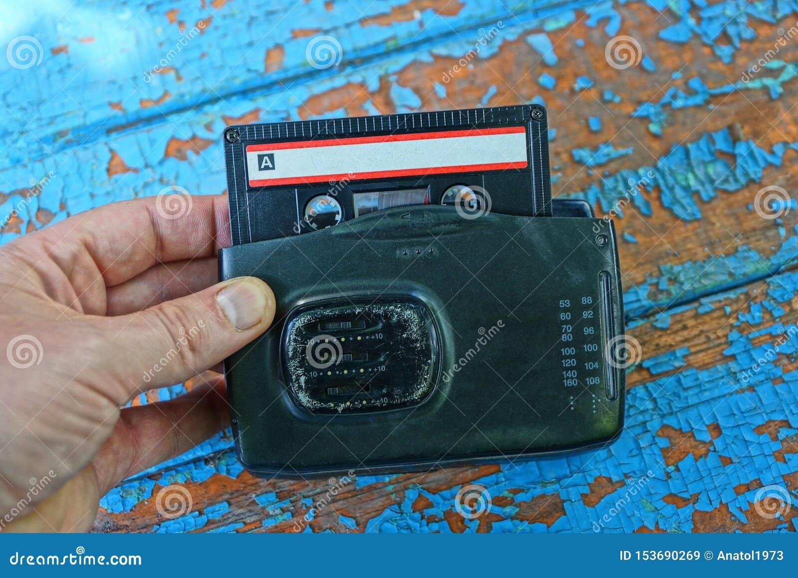 手拿着有卡式磁带的老黑人音频球员
